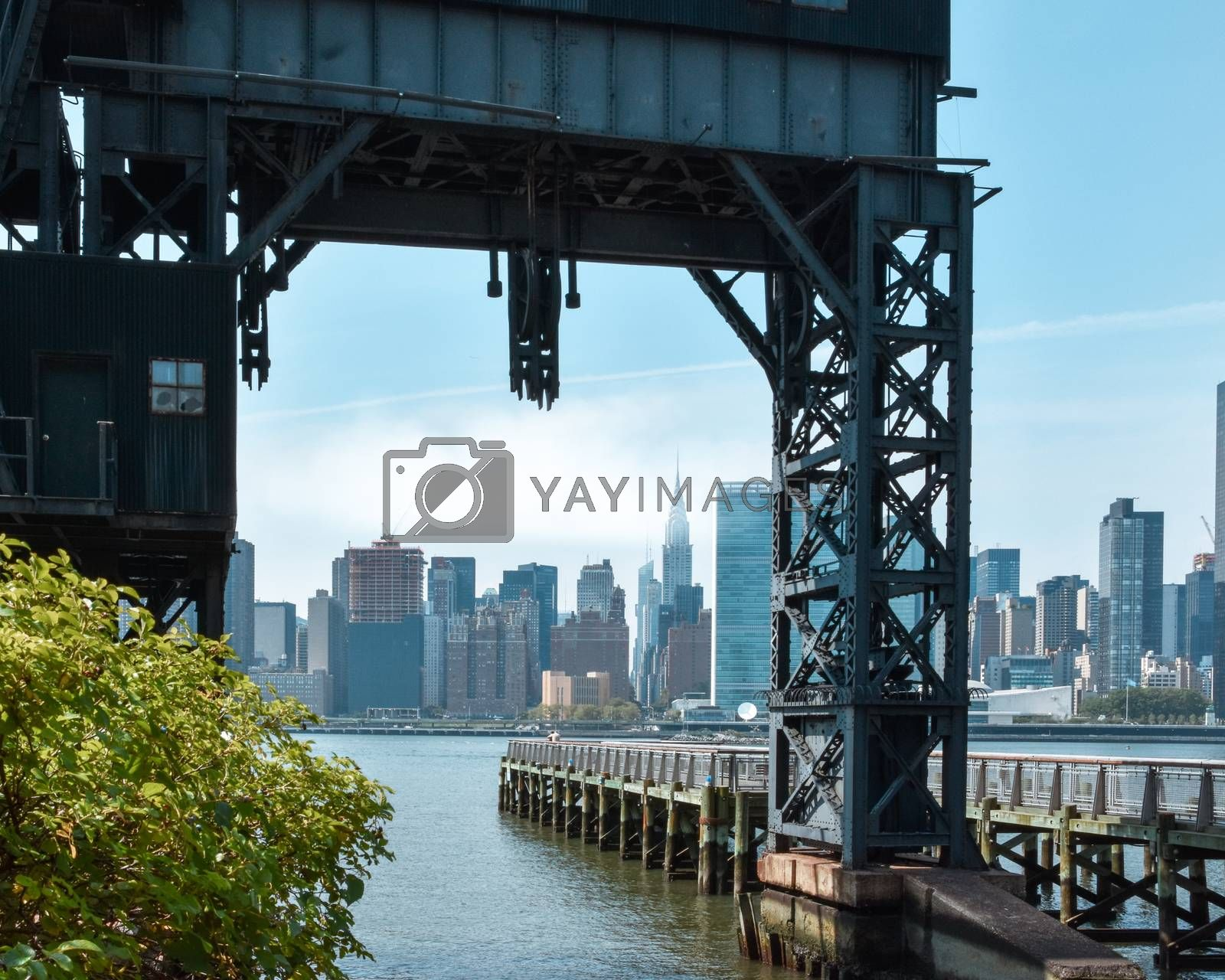 Office buildings and apartments on the horizon through the Ferry Dock at Long Island. Real estate and travel concept. Brooklyn, New York City, USA