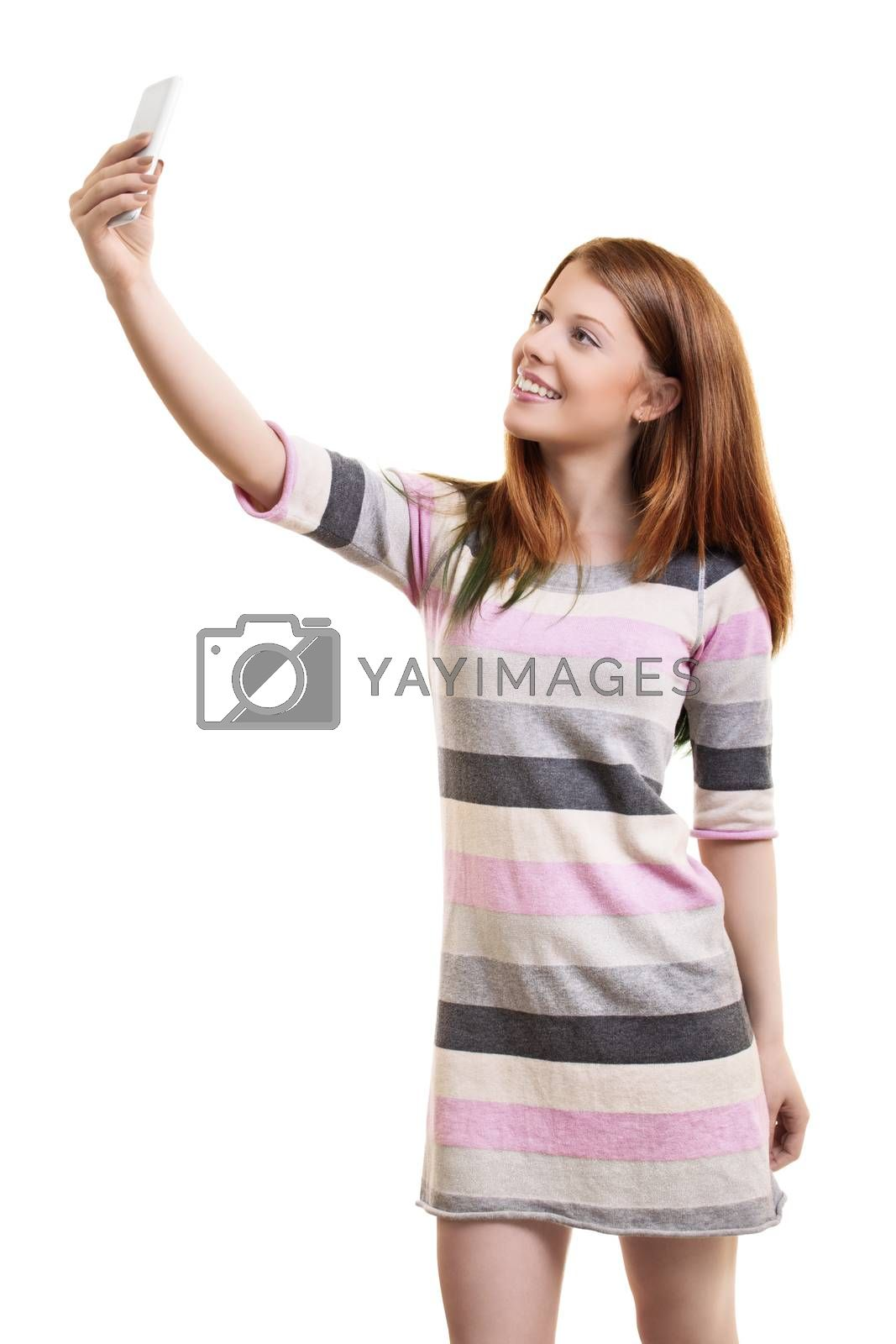 Beautiful smiling fashionable young woman in a casual dress taking a selfie with a smartphone, isolated on a white background. Full body length portrait, isolated on white background.