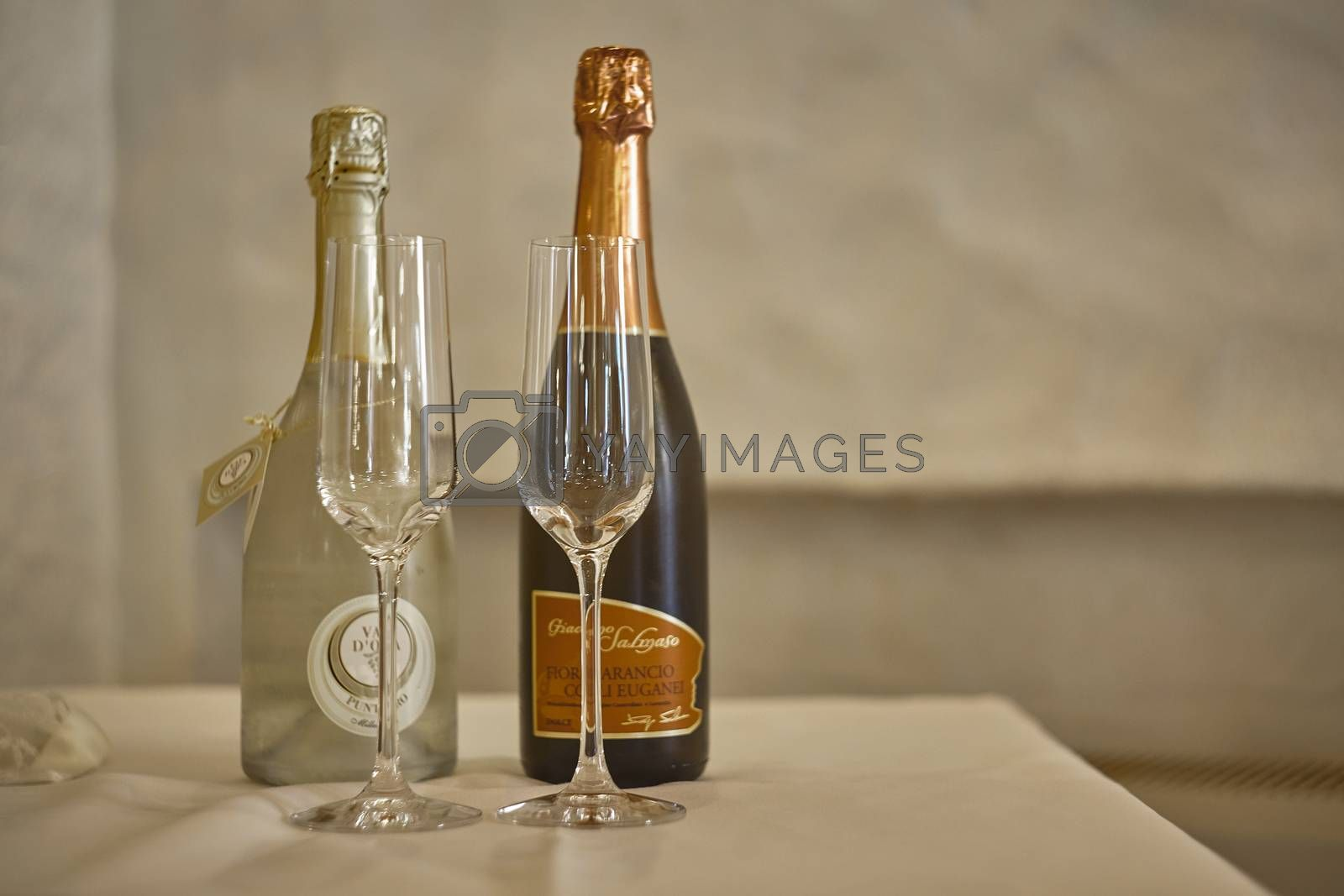 Two wine bottles and two clean glasses on the table await the toast for the festivities