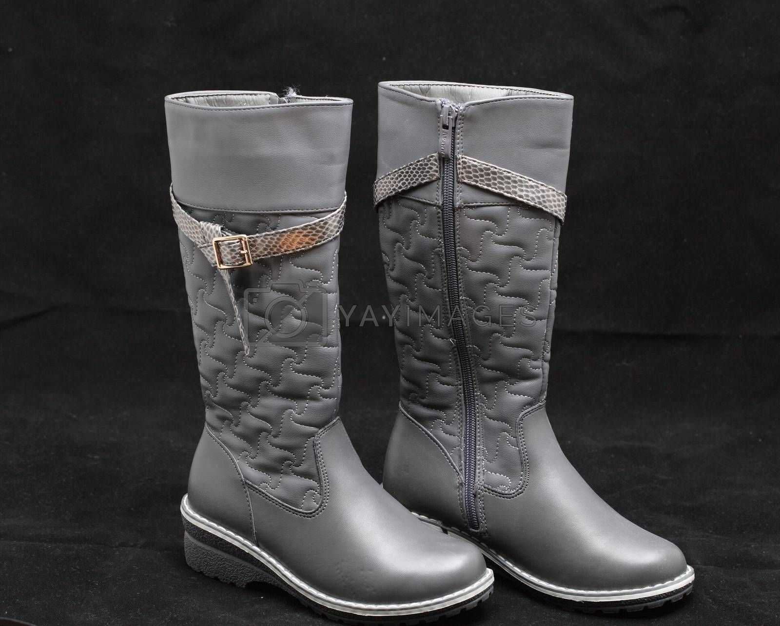 gray women's boots on black background