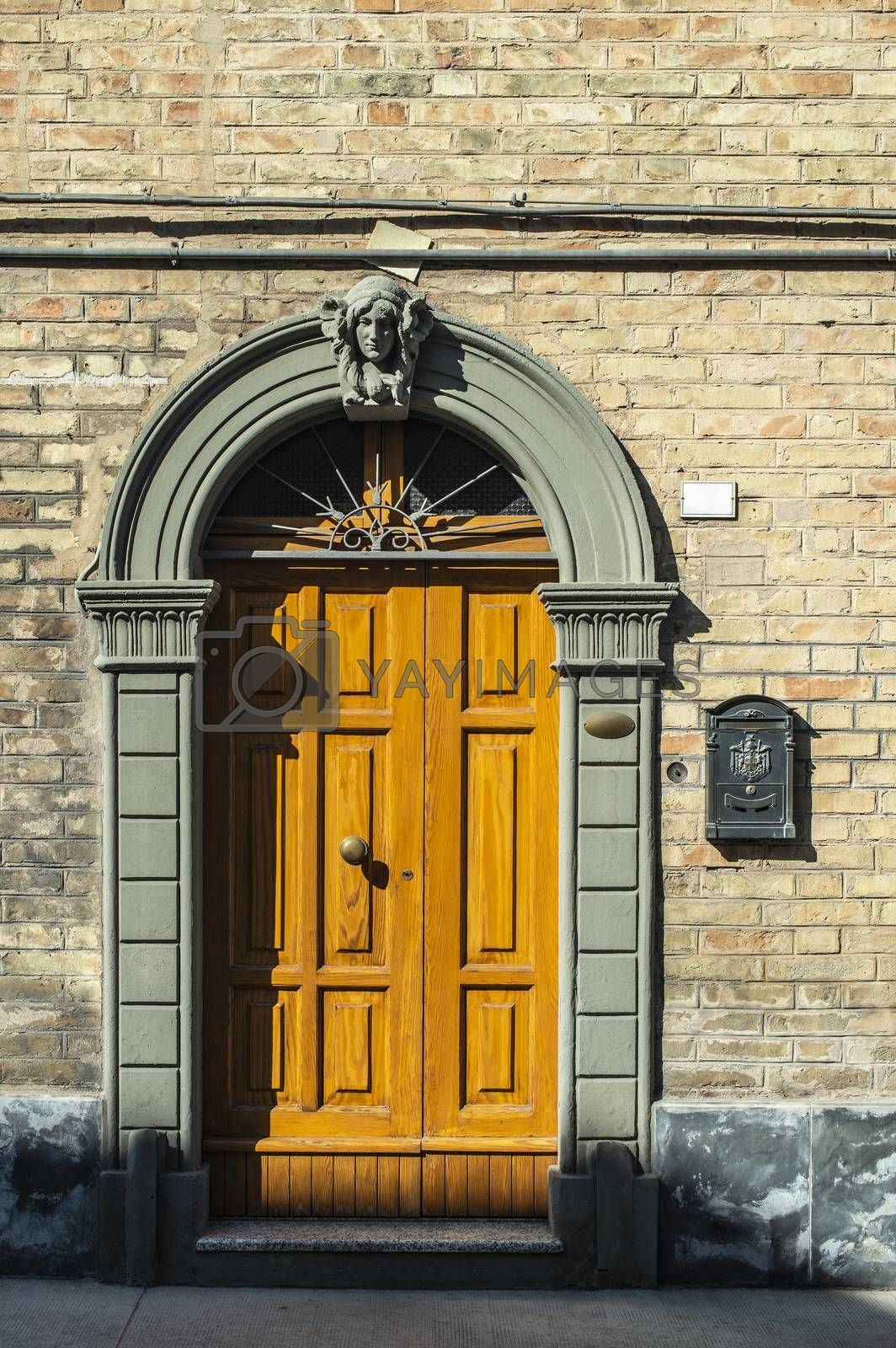 Old typical italian wooden door. Italian house. Ancient house facade. Sunlight. Round door arch. Stone build house. Wrought iron door handles.
