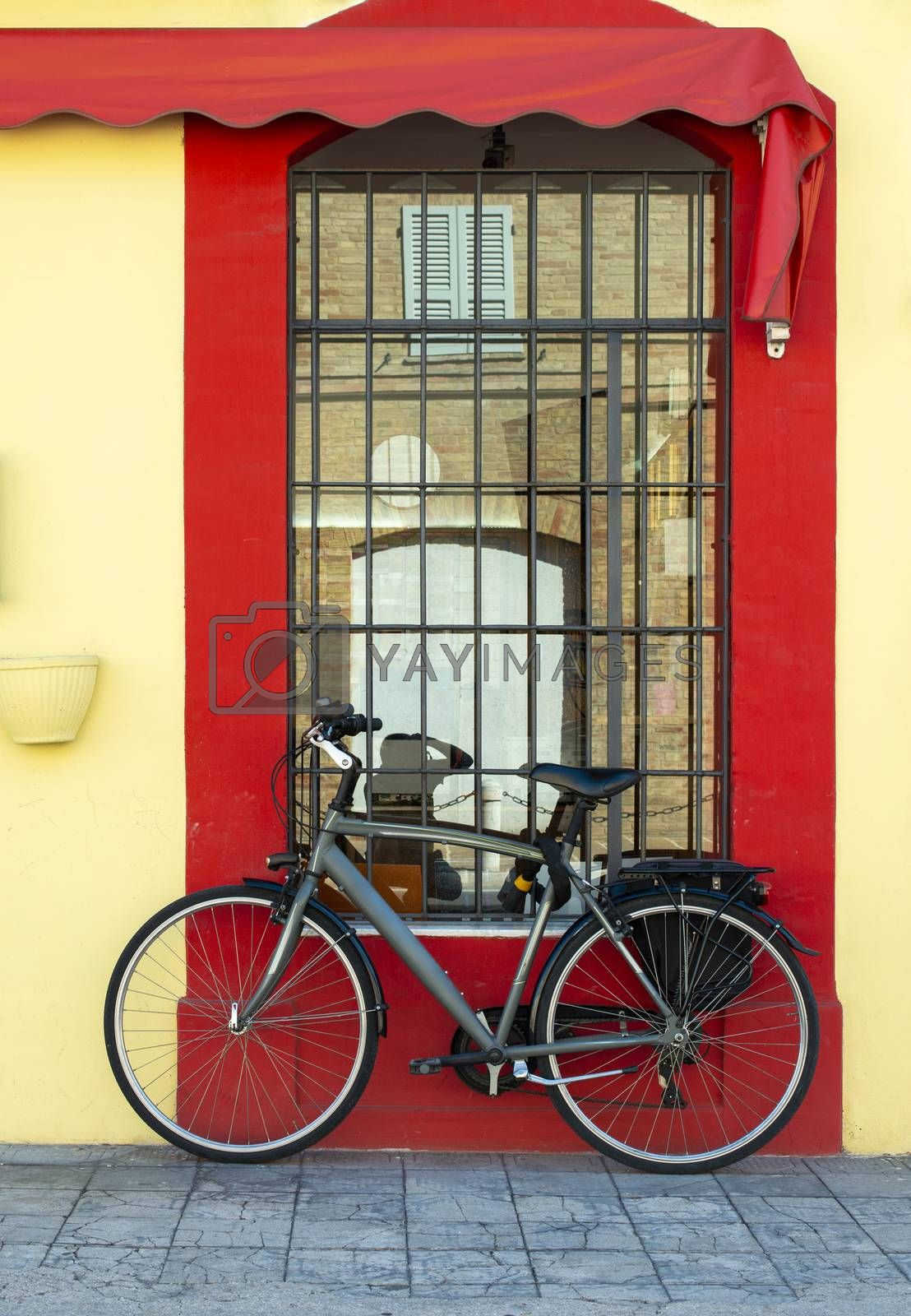 Grey bike in front of yellow facade and red window. Bicycle with trunk. Reflection of old building in the window. Window with grille.