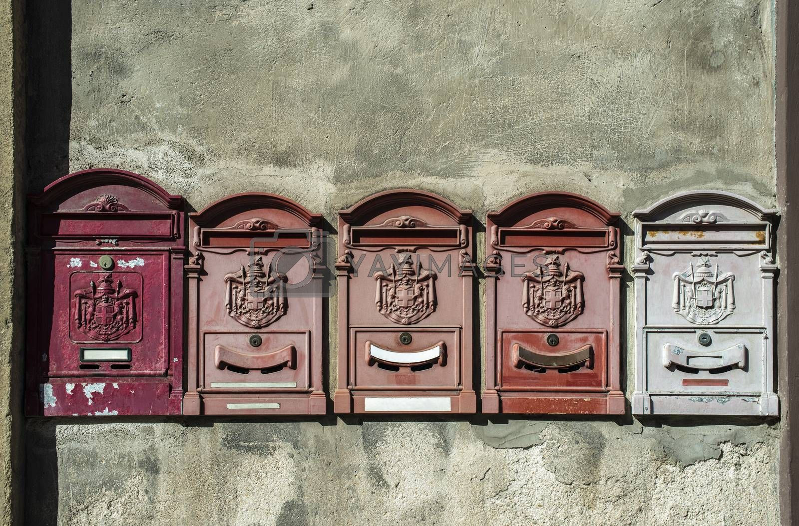 Old vintage mailboxes in Italy. Metal red mailboxes on grey facade. Hard sunlight. Empty plates. Italian house wall. Vintage mail correspondence concept.