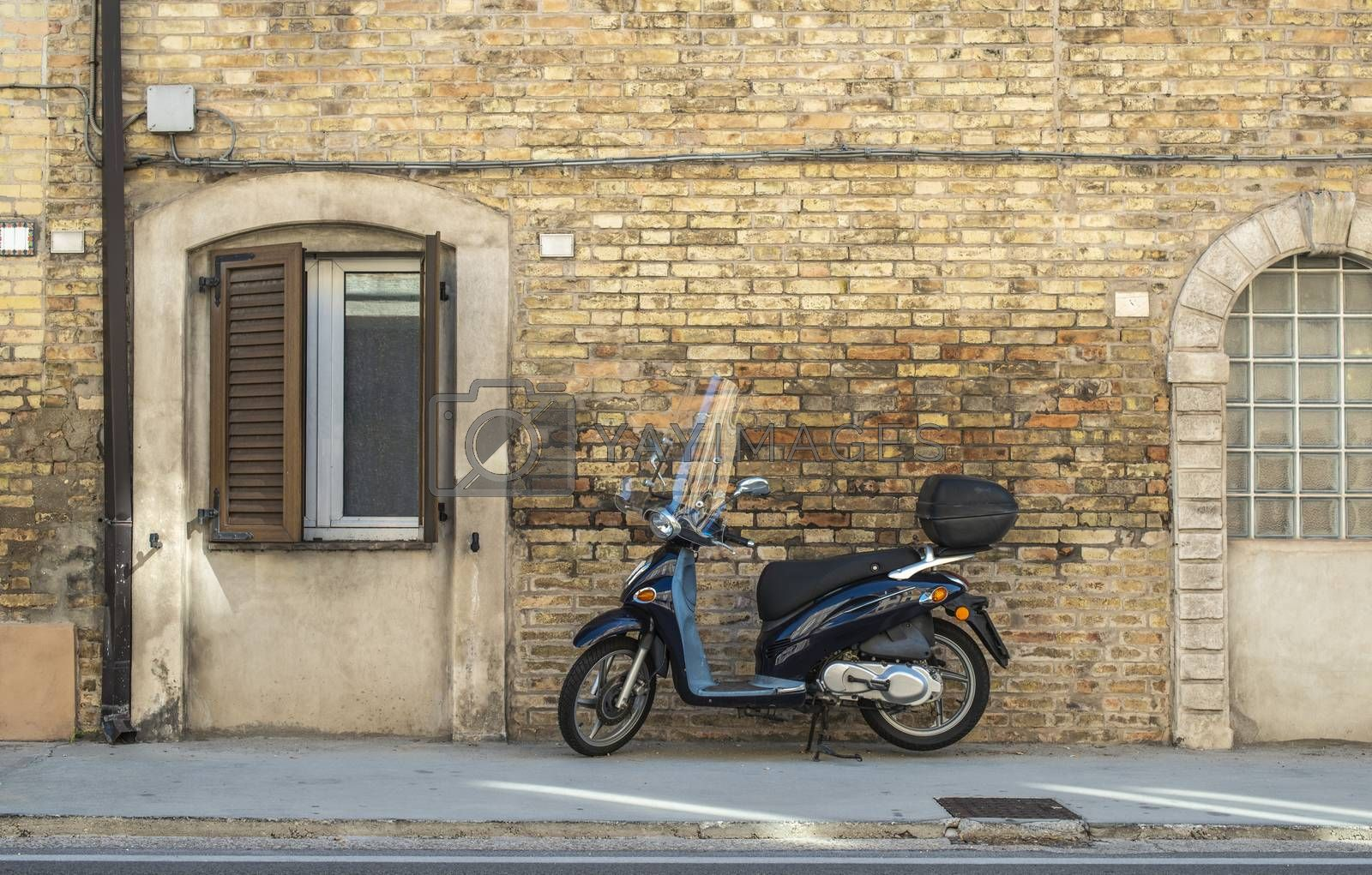 Typical italian motorbike in front of old house facade. Traditional bike and ancient mediterranean architecture.