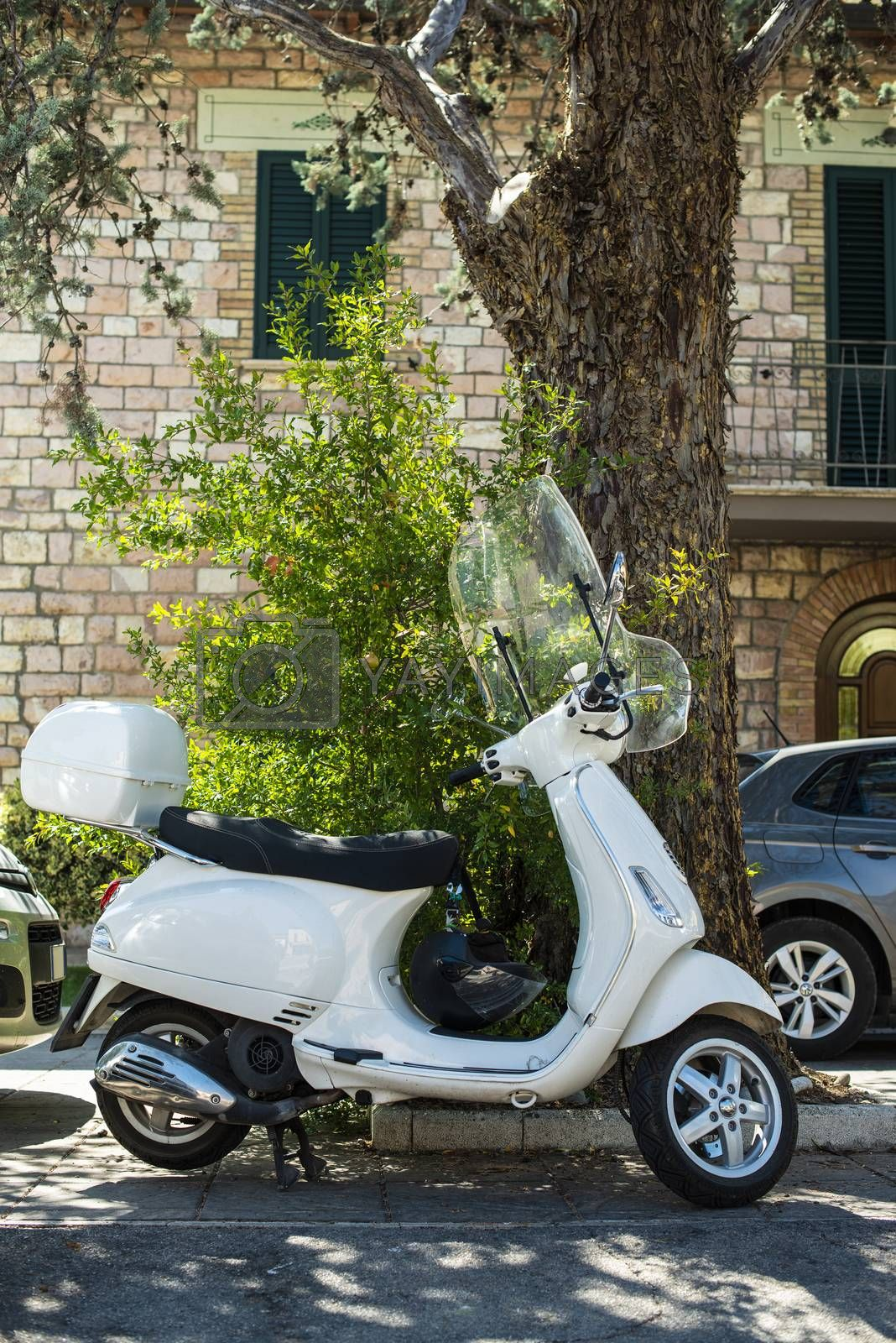 Typical italian motorbike in front of old house facade. Traditional white bike and ancient mediterranean architecture.