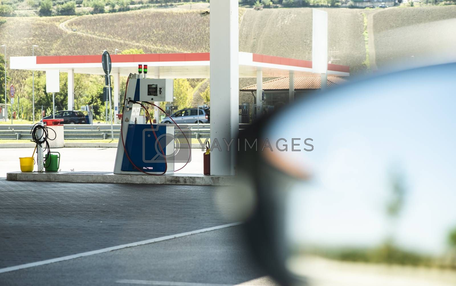 Gas station. Refueling car with Refueling car with gas pressure fuel. Gas loading column.  Car mirror.