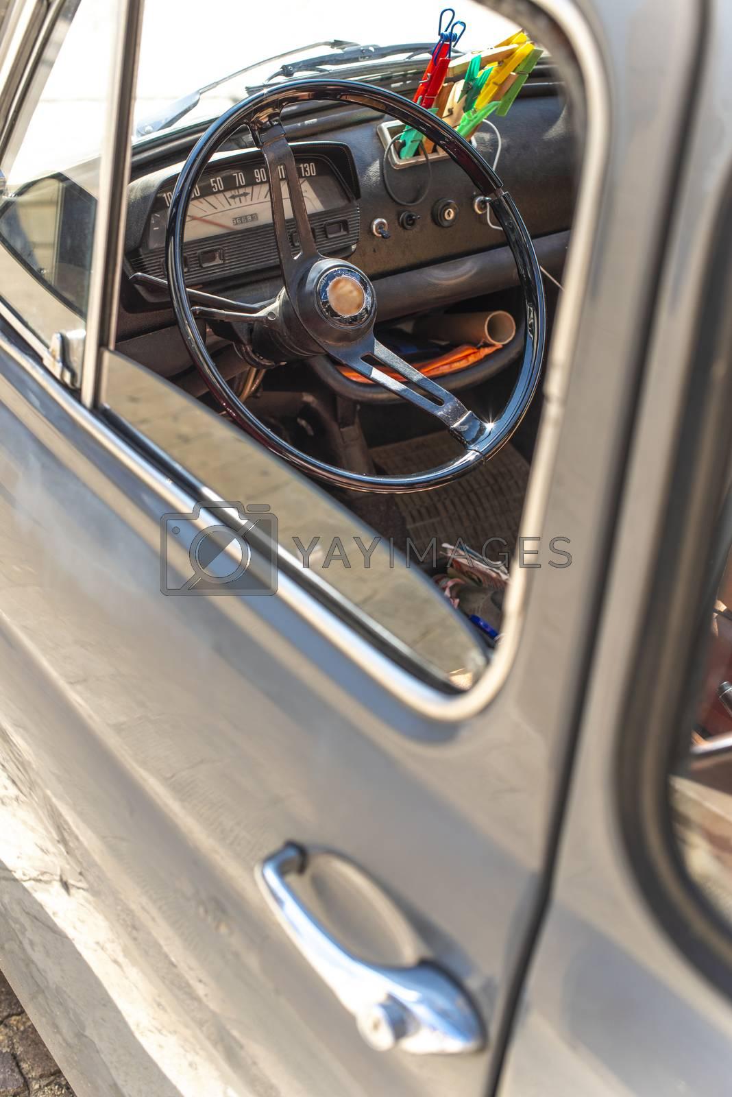 Steering wheel on vintage car. View from the door window. Opened window on old vintage car.