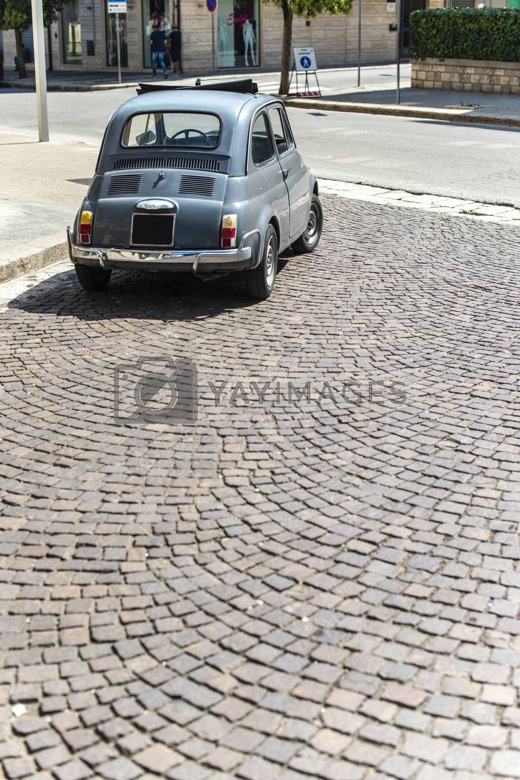 Vintage small car on traditional italian paved street. Dark grey old car.