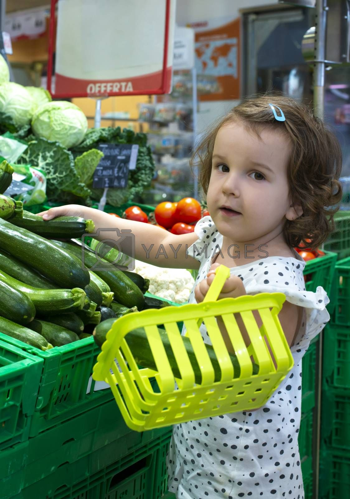 Little girl buying zucchini in supermarket. Looking at the camera. Child hold small basket in supermarket and select vegetables. Concept for healthy eating for children.
