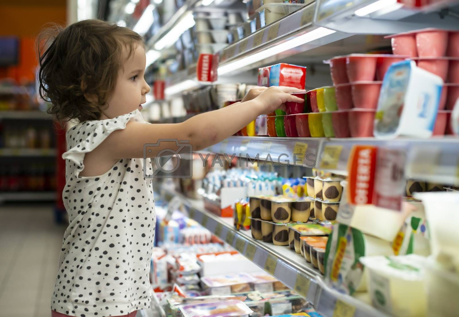 Little girl buying yogurt in supermarket. Child in supermarket select products from store showcase. Concept for children selecting milk products in shop.