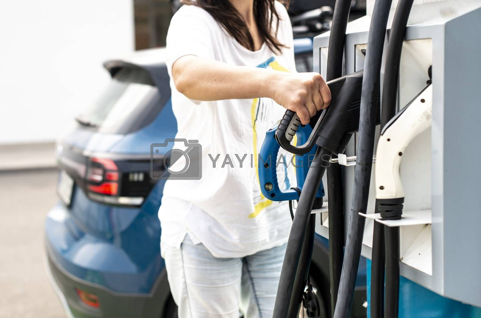 Woman charge her Electric car on gas station. Blue car and electric plug for charging. Ecology fuell concept.