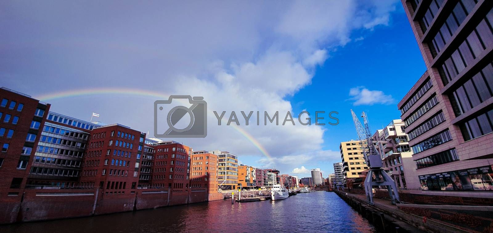 Beautiful rainbow over Hamburg canal. Beautiful wide angle view from the Kaiserkai bridge on the water canal at the Speicherstadt warehouse district near the Elbphilharmony concert hall. Buildings constructed with steel and brick.