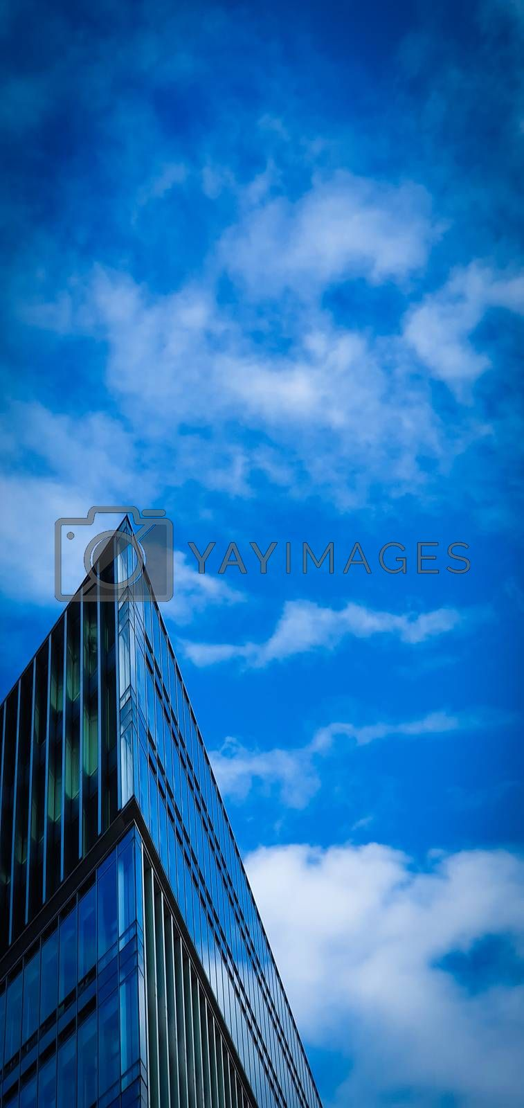 Modern Architecture. Minimal Aesthetics. Low angle view of a futuristic triangular building against a clear blue sky background. Corner building.