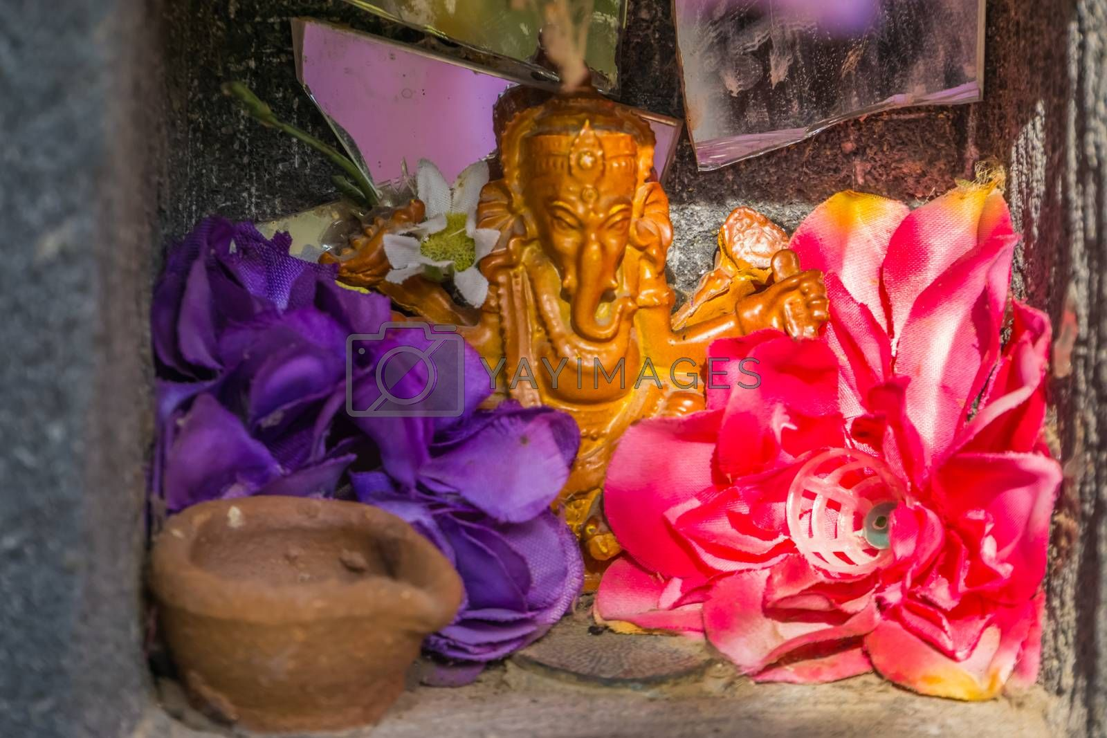 beautiful small Indian altar with flowers and a Ganesha sculpture, Religious background by charlotte Bleijenberg