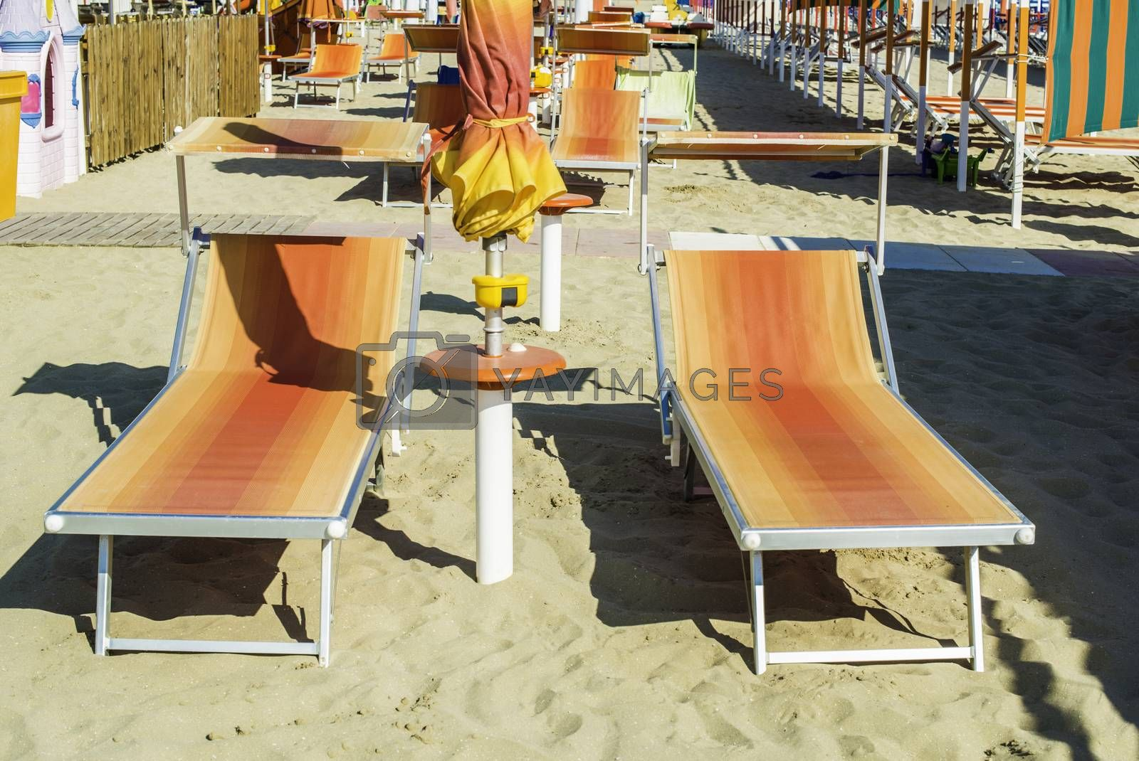 Orange sunbeds and umbrellas on the beach.