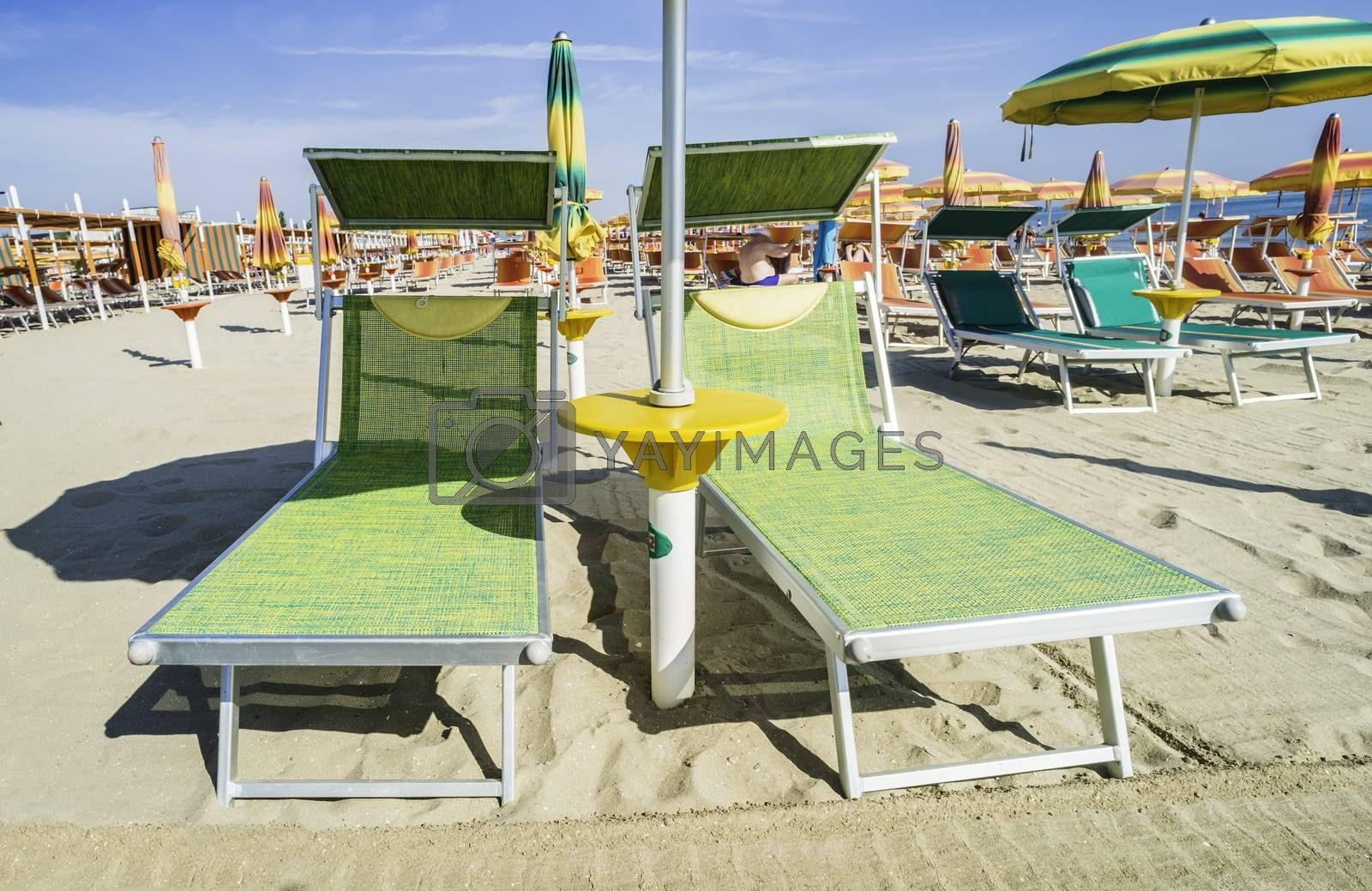 Green sunbeds and umbrellas on the beach.