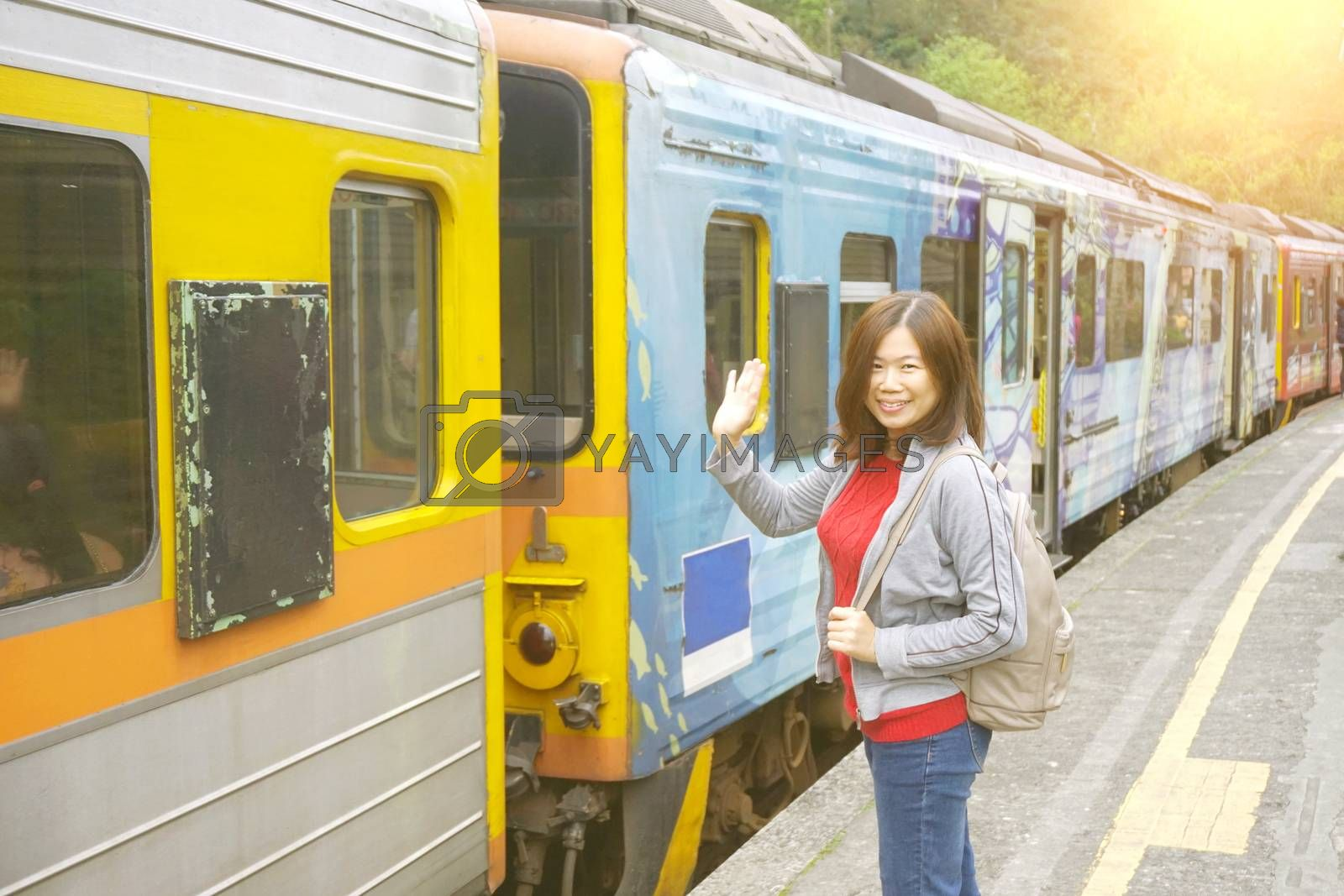 Asia backpacker woman feeling happiness and greeting his friend before getting on the train at the Pingxi Line historic train station in Taiwan . Travel and transportation concept.