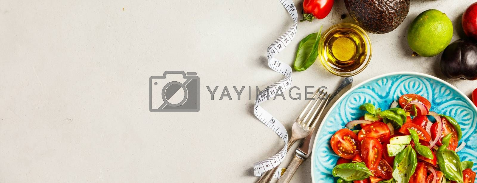 Tomato, basil, avocado and onion salad in blue plate for vegan, gluten free, allergy-friendly, clean eating or raw diet. Grey concrete background and top view