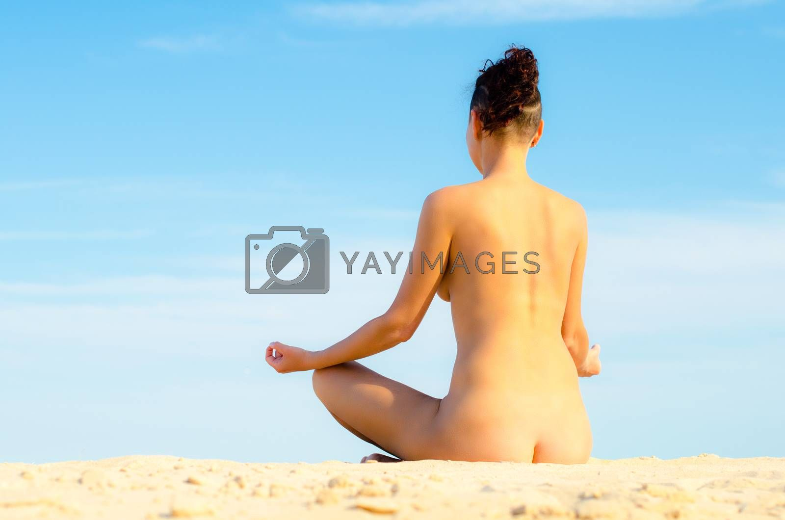 naked young girl sitting in a yoga pose on the sand on the beach by Gera8th