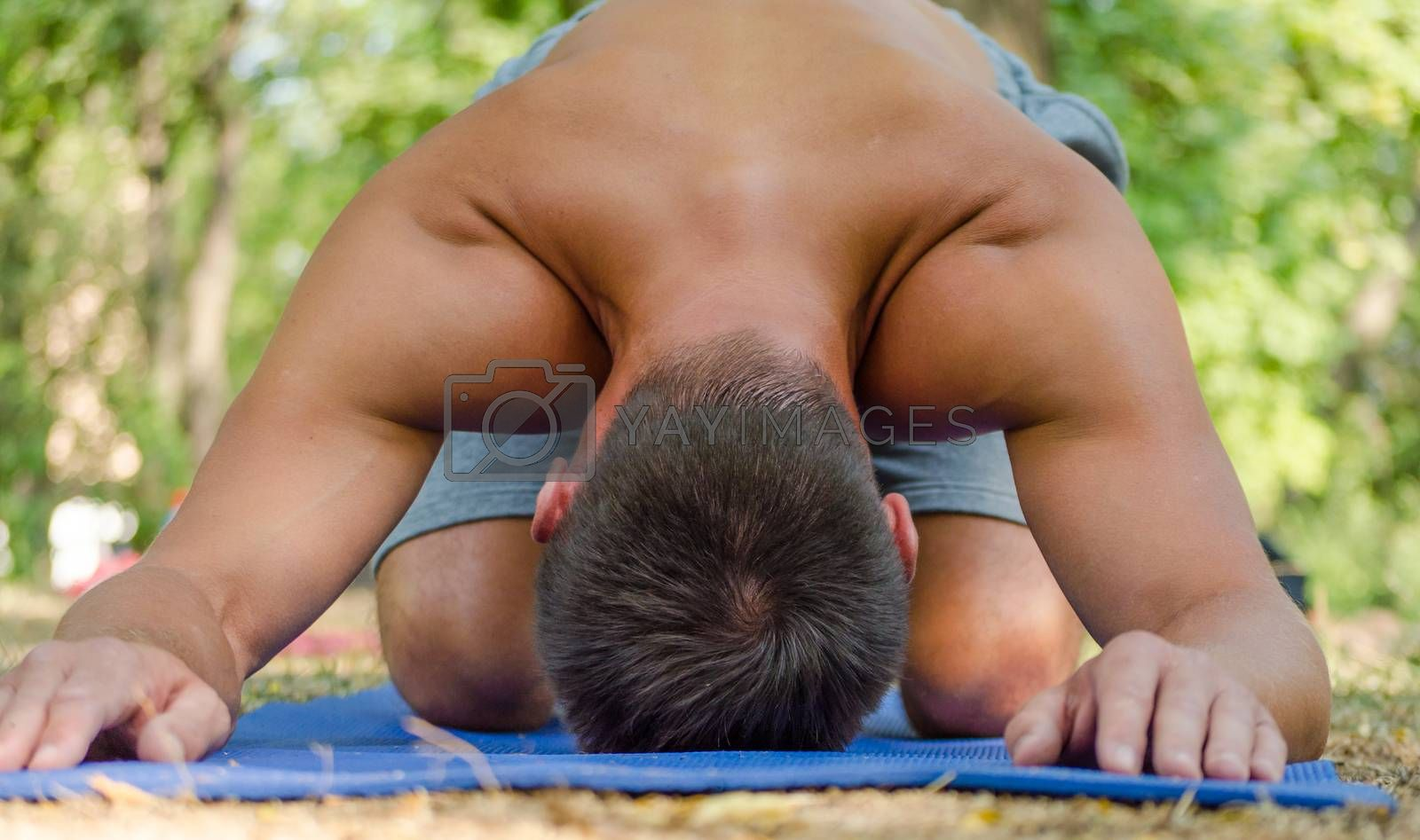 young athletic man in balasana yoga pose on a blue mat by Gera8th