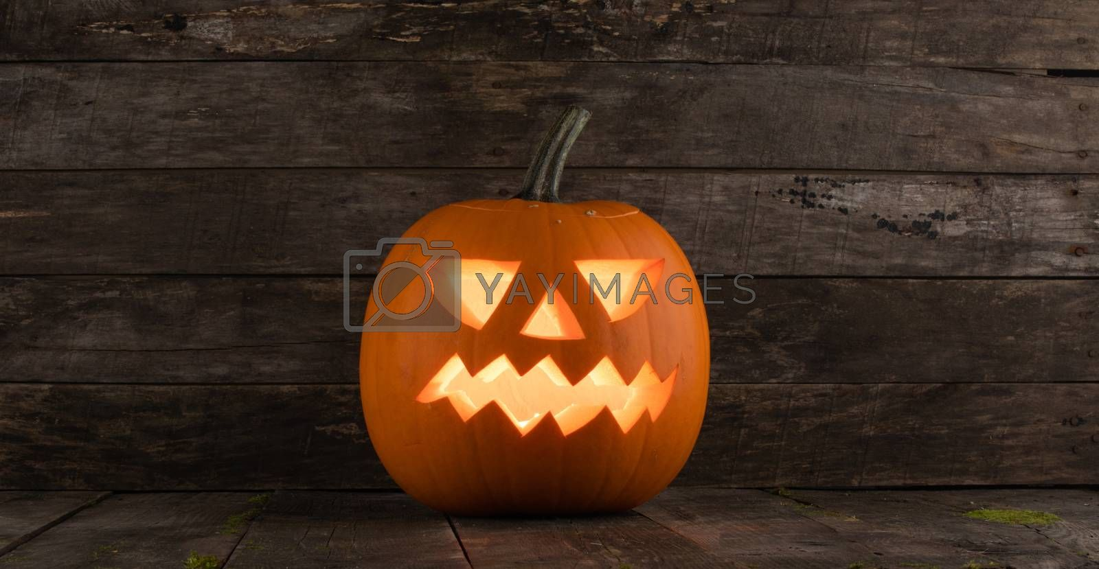 Glowing Halloween pumpkin head jack lantern on old wooden background