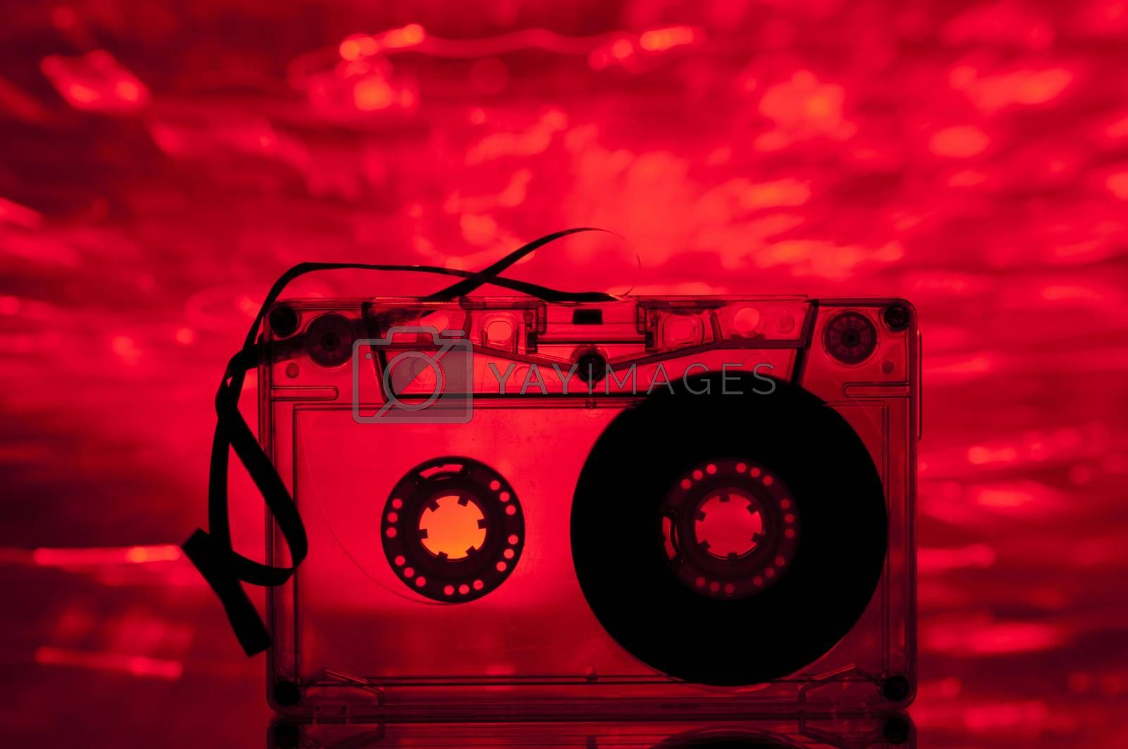 Cassette tape and multicolored lights on background