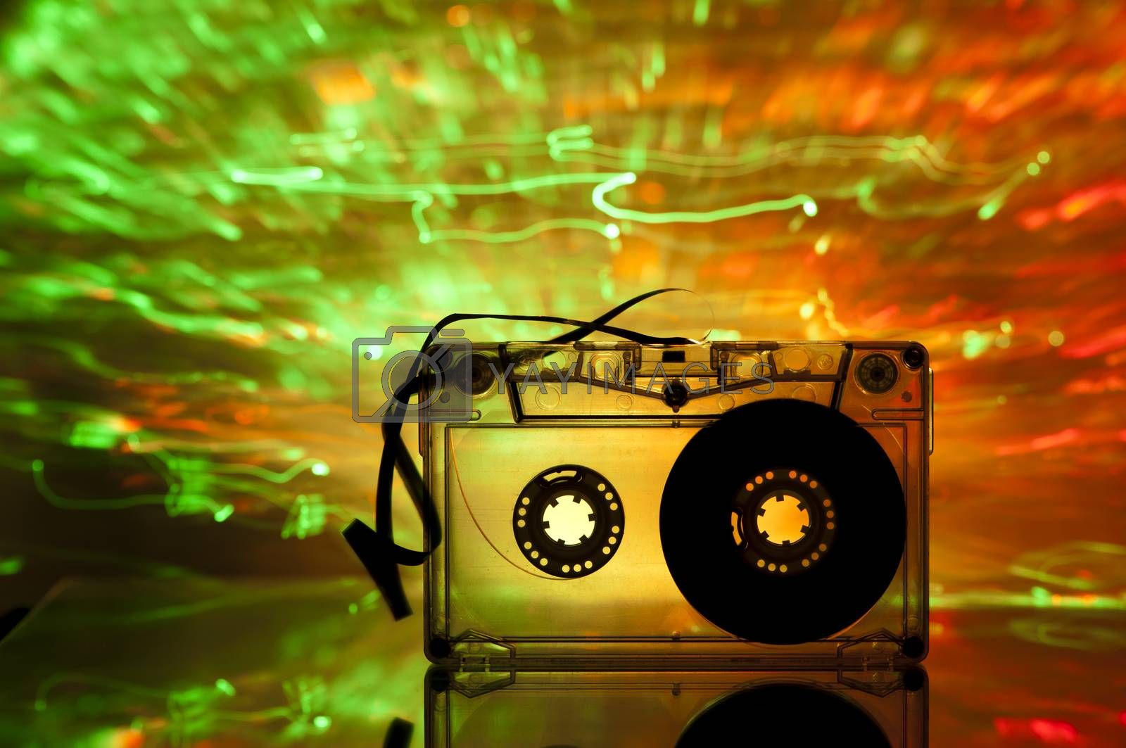 Cassette tape and multicolored yellow green lights on background