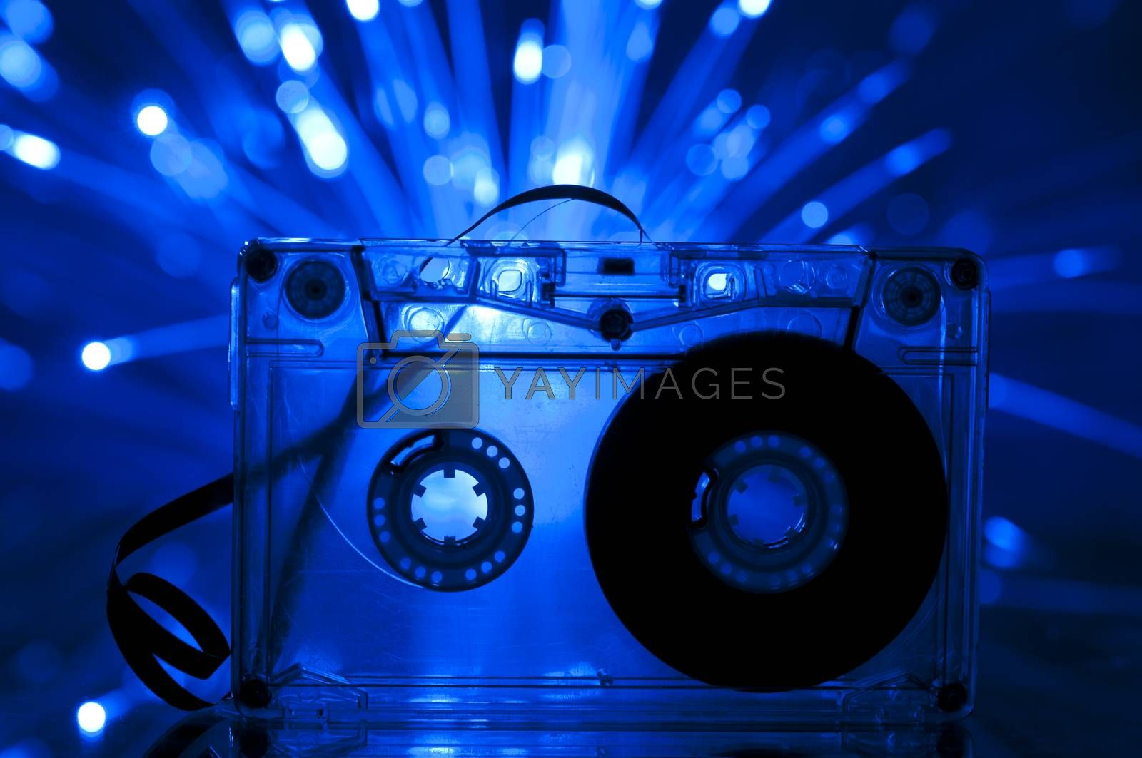 Cassette tape and multicolored blue lights on background