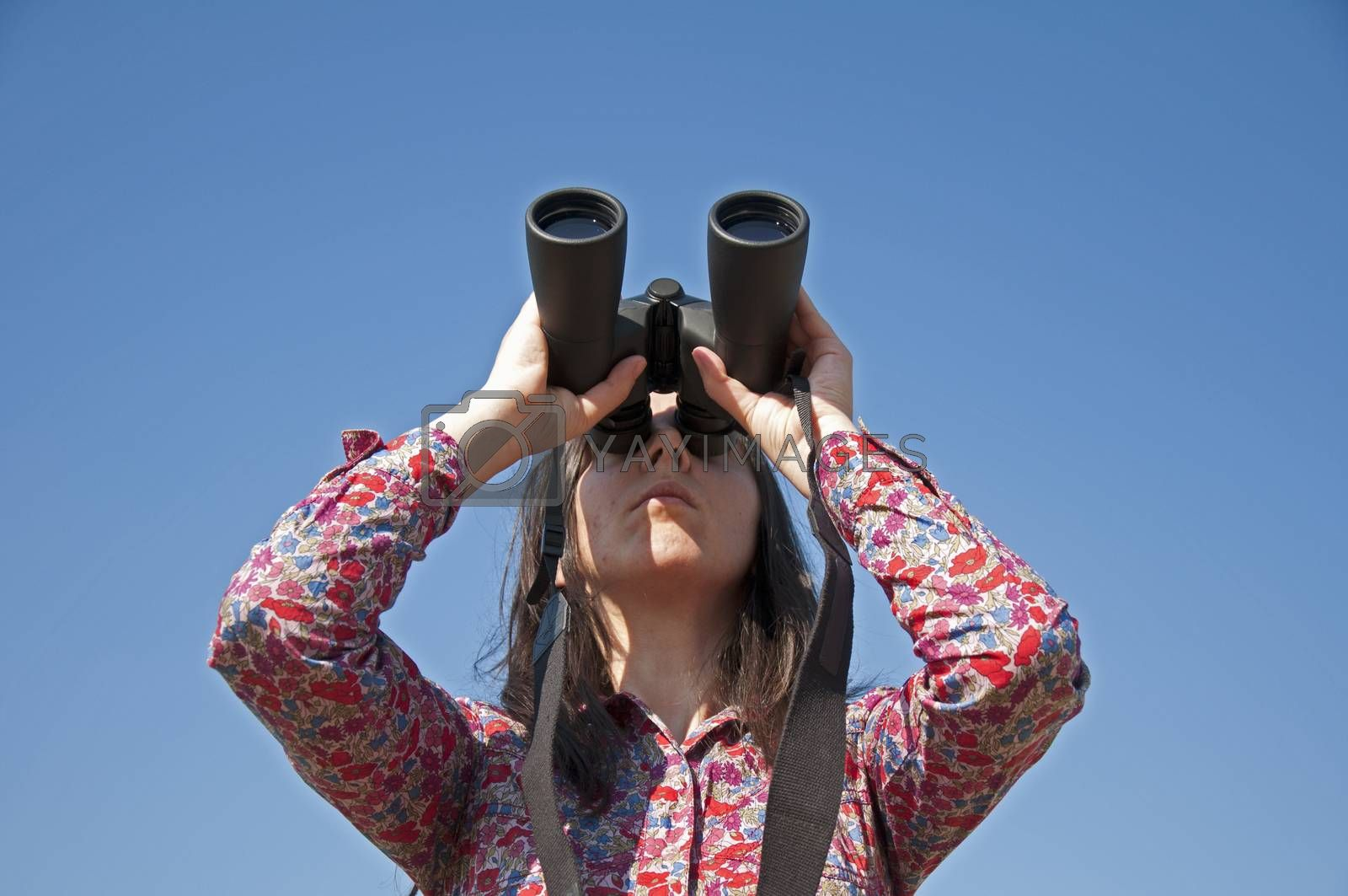 Young woman using binoculars. On blue sky background