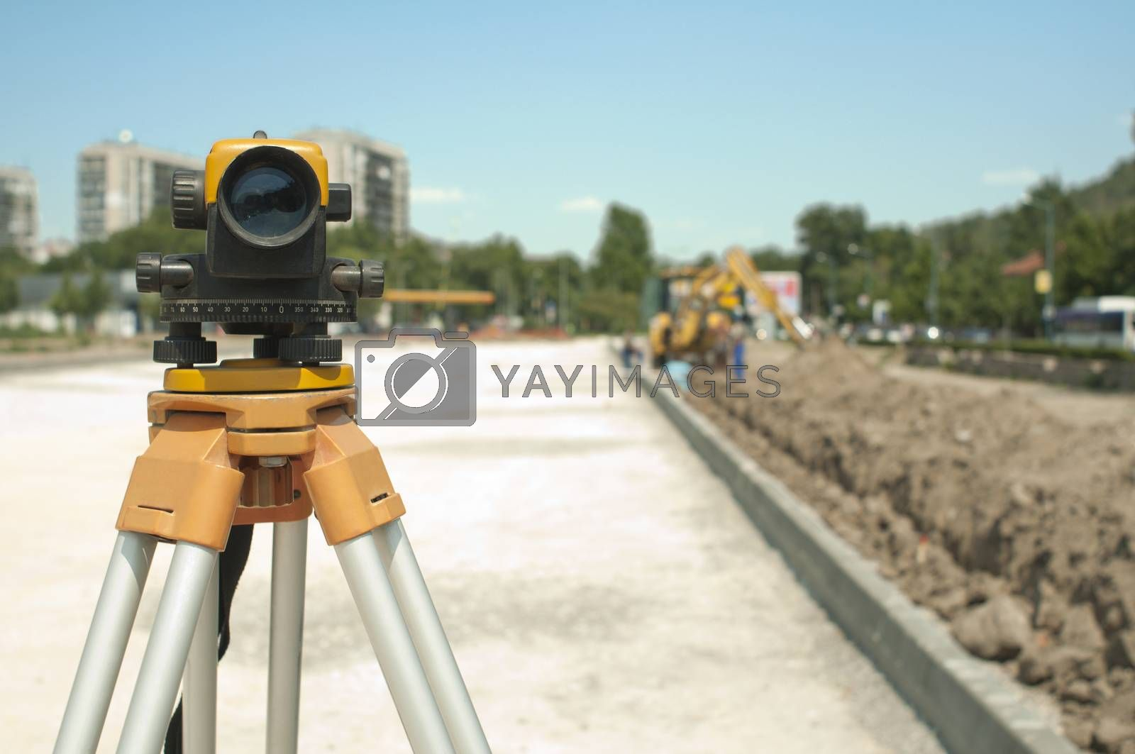Surveying equipment to infrastructure construction project. Excavator on the background