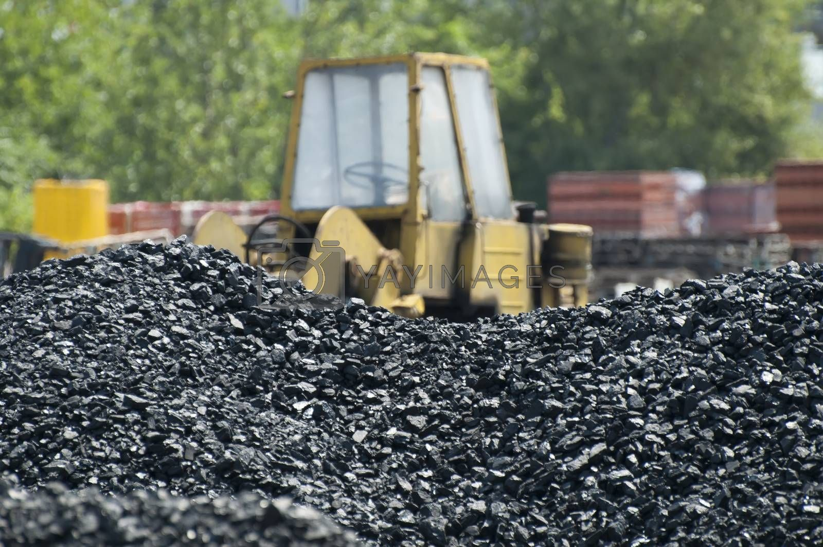 Coal piles and Excavator on background