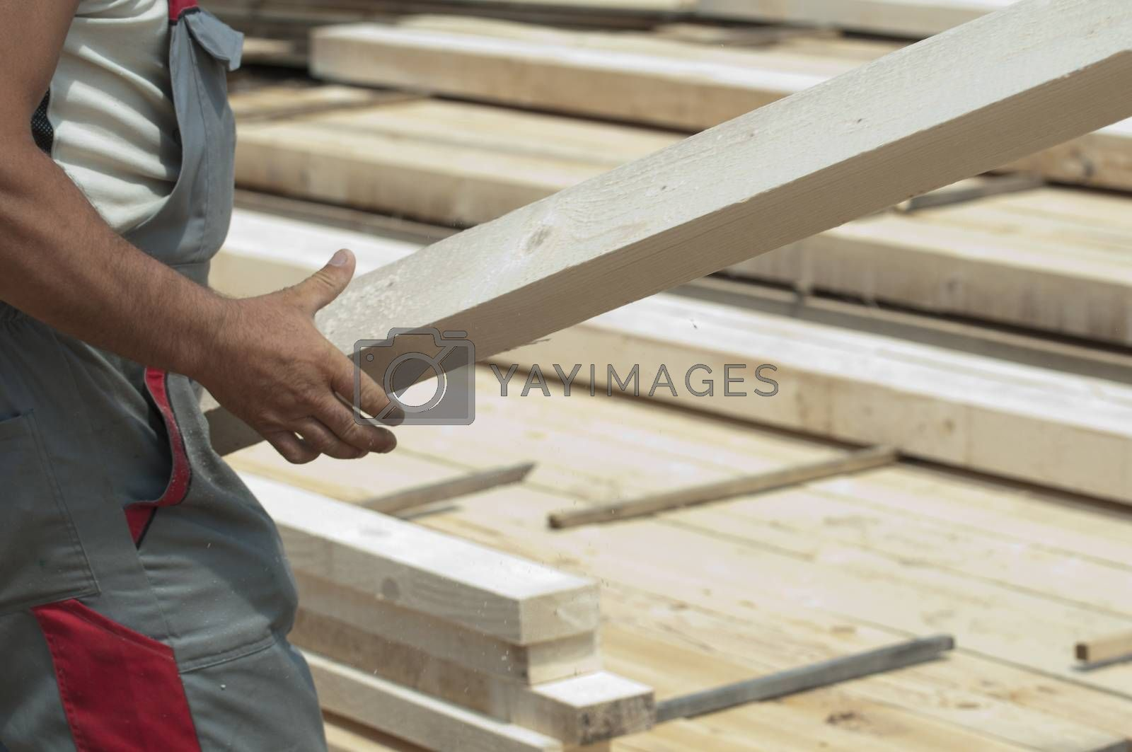 A worker moves a wooden beam
