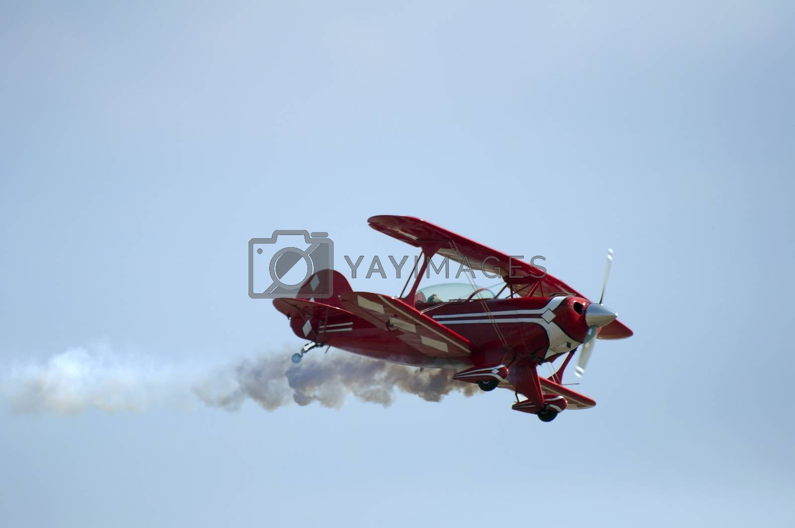Red plane looping in a blue sky. Close up