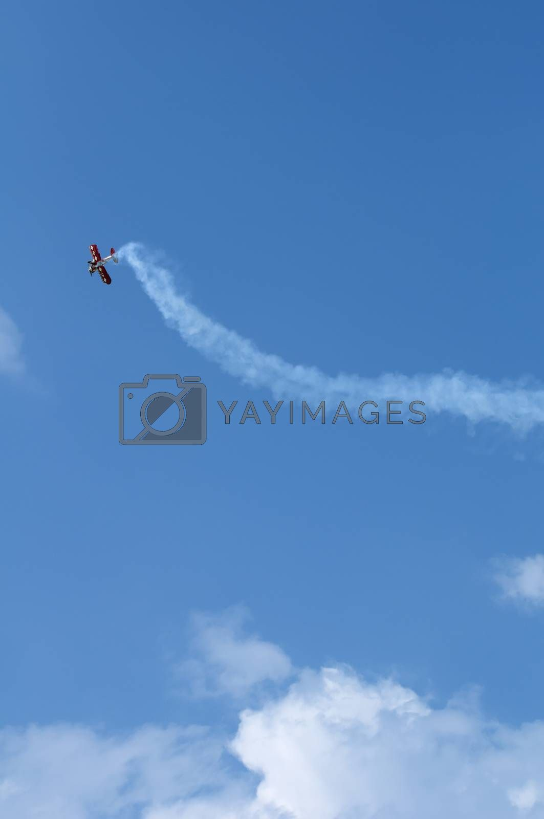 Plane doing Loops on blue cloudy sky