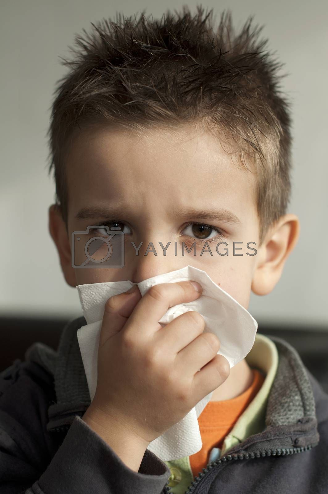 Child suffering from a cold. Cough with a tissue