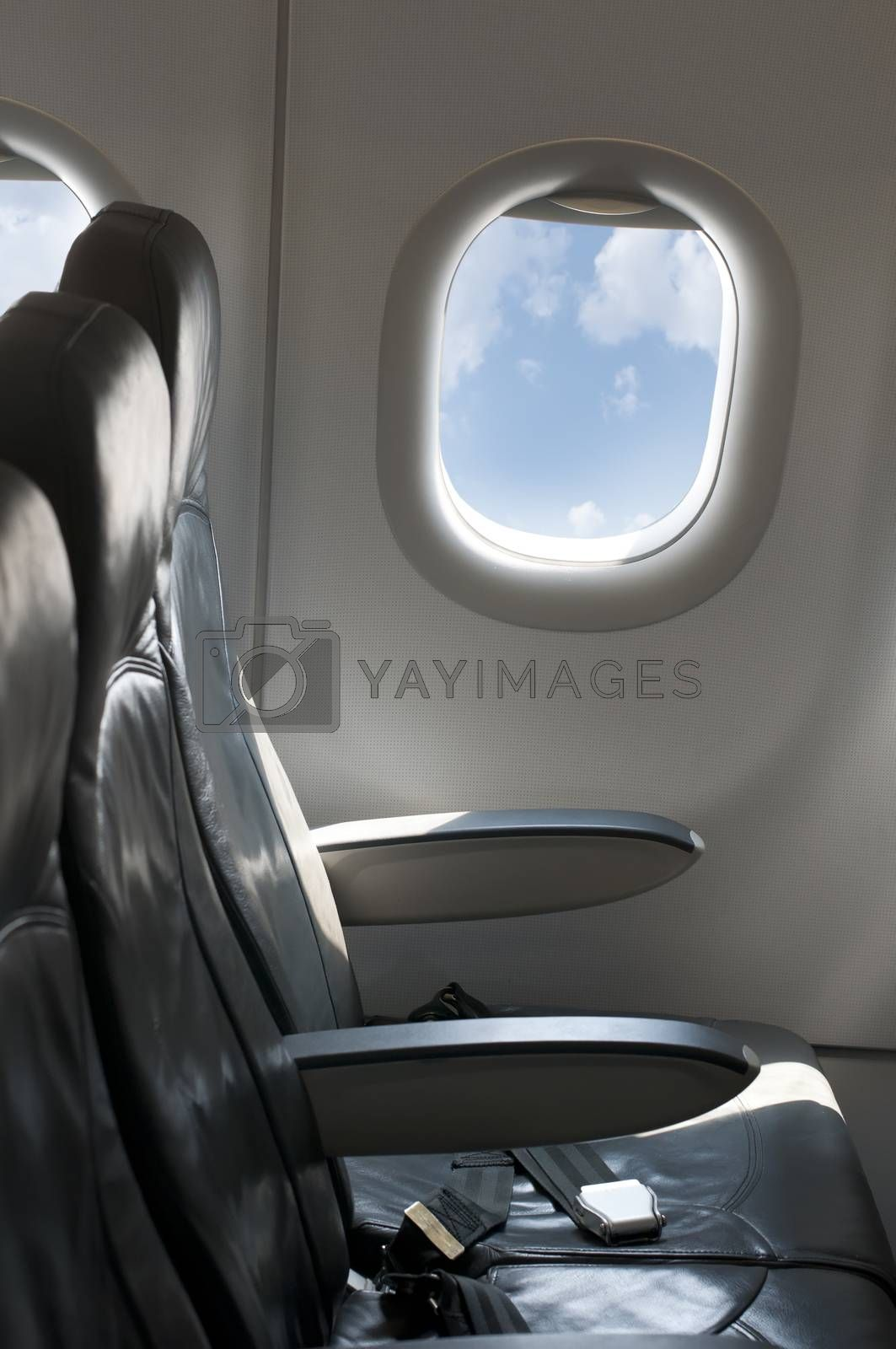 Inside an empty plane. Window and blue cloudy sky