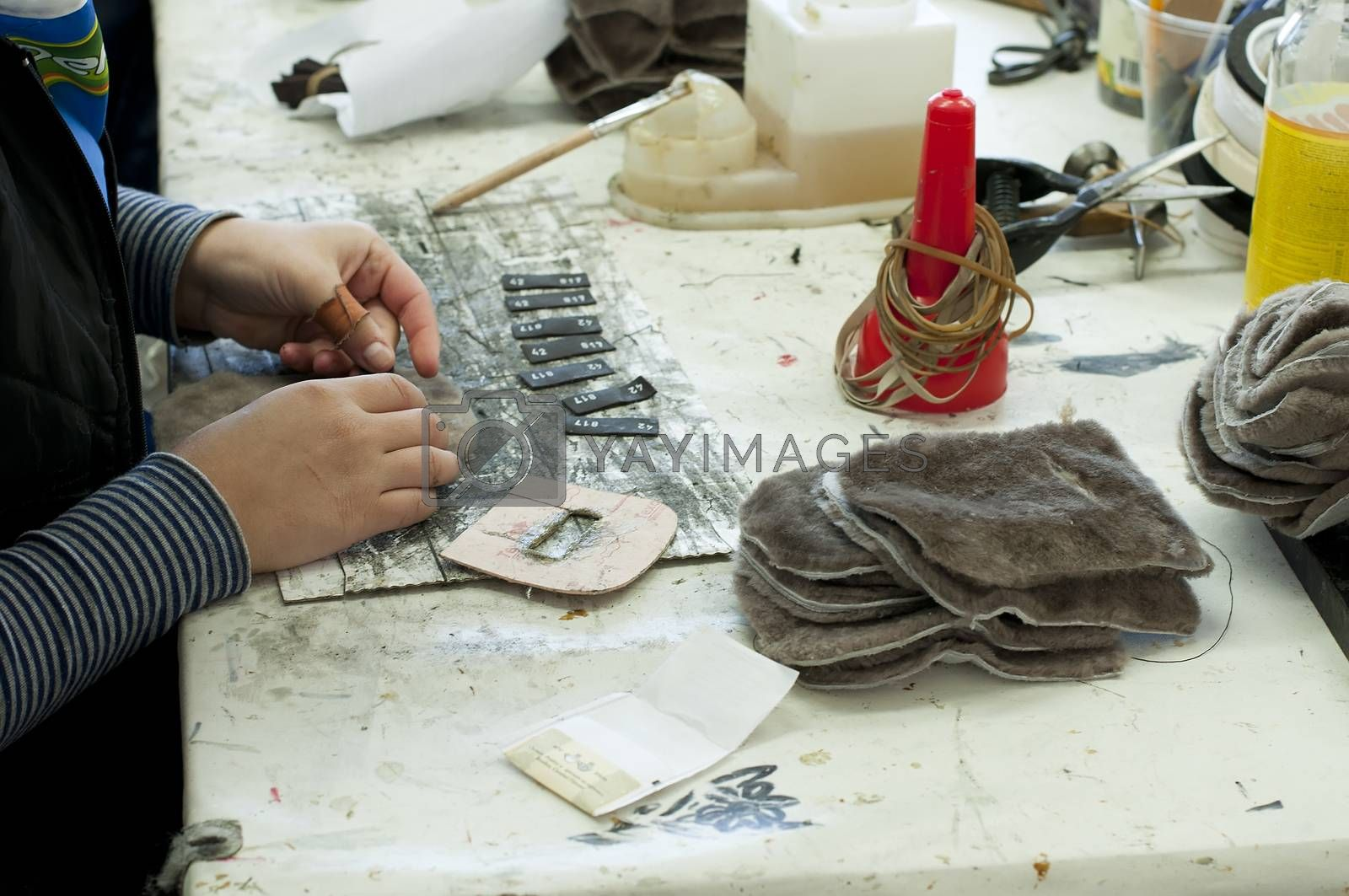 Handmade manufacture of footwear.Cropping of logos for shoes