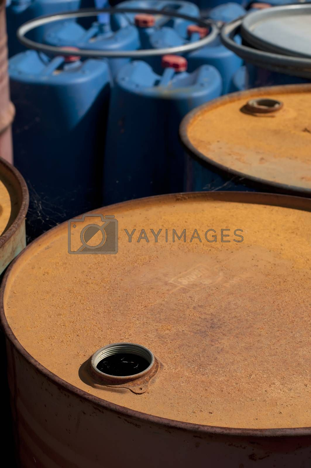 Old colored barrels for oil products. Empty rusted drums and blue canisters