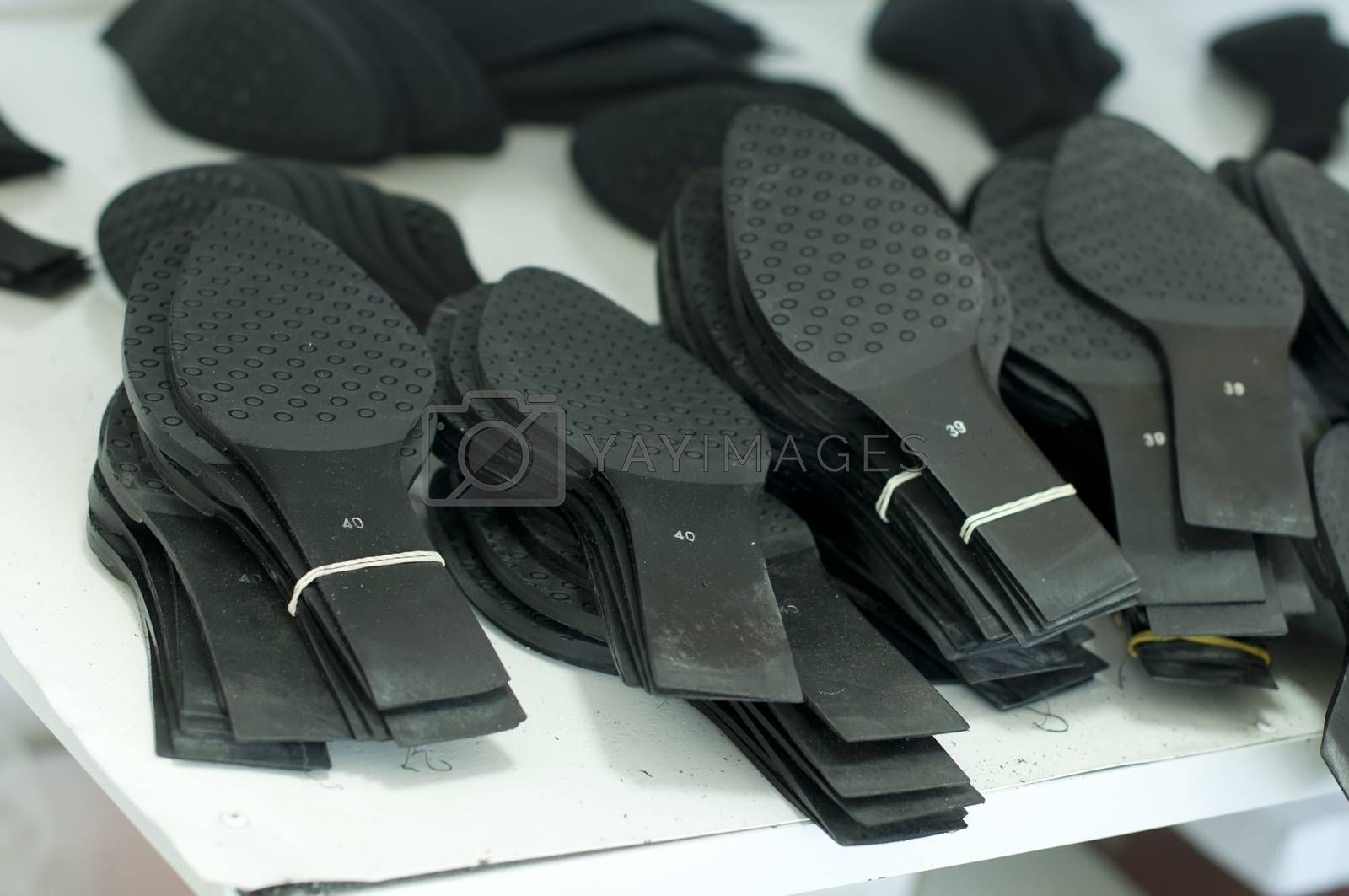 Black shoe soles in a factory