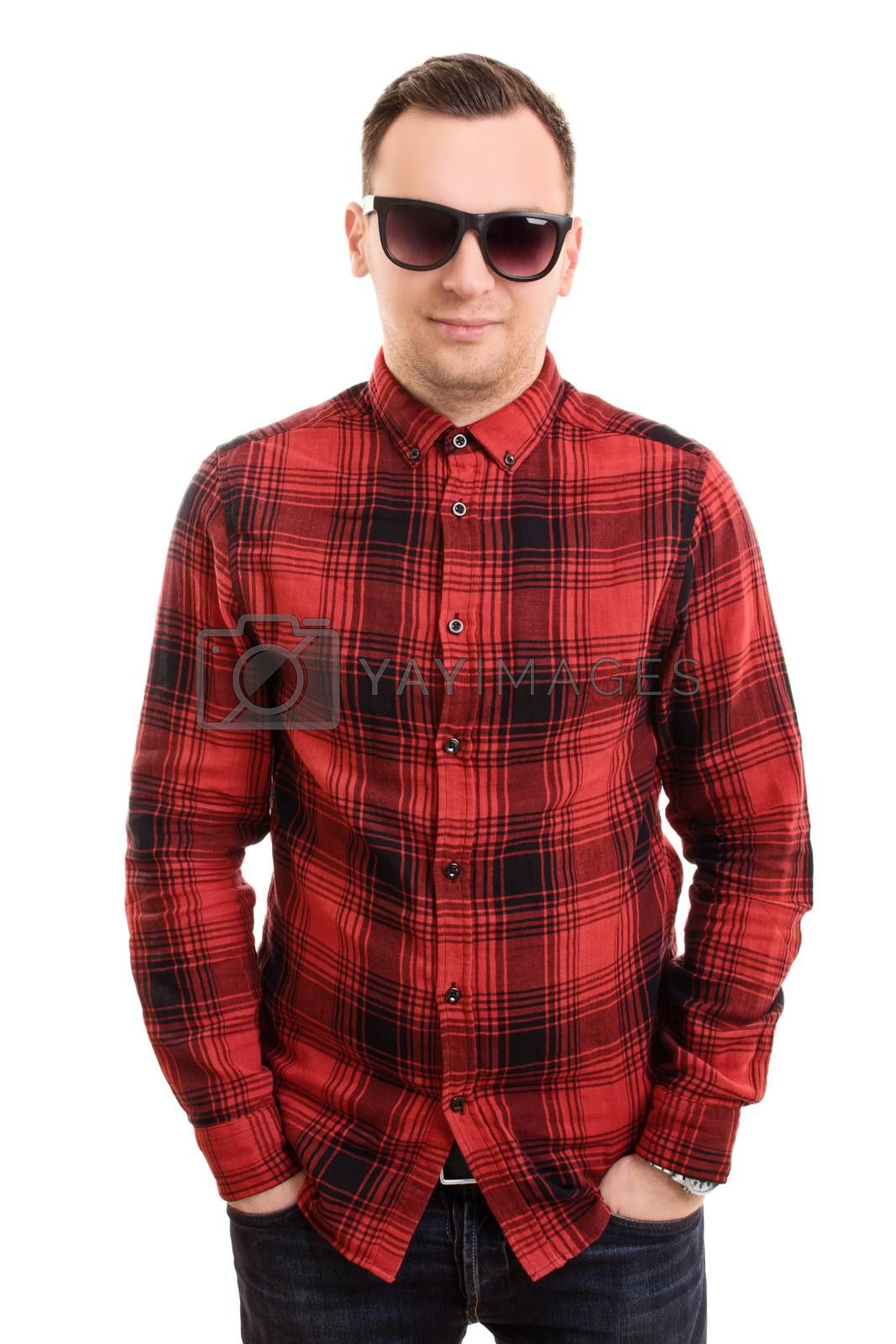 Modern and casual in style. Fashion portrait of stylish handsome young man in plaid shirt and sunglasses, posing with hands in pockets, isolated on white background.
