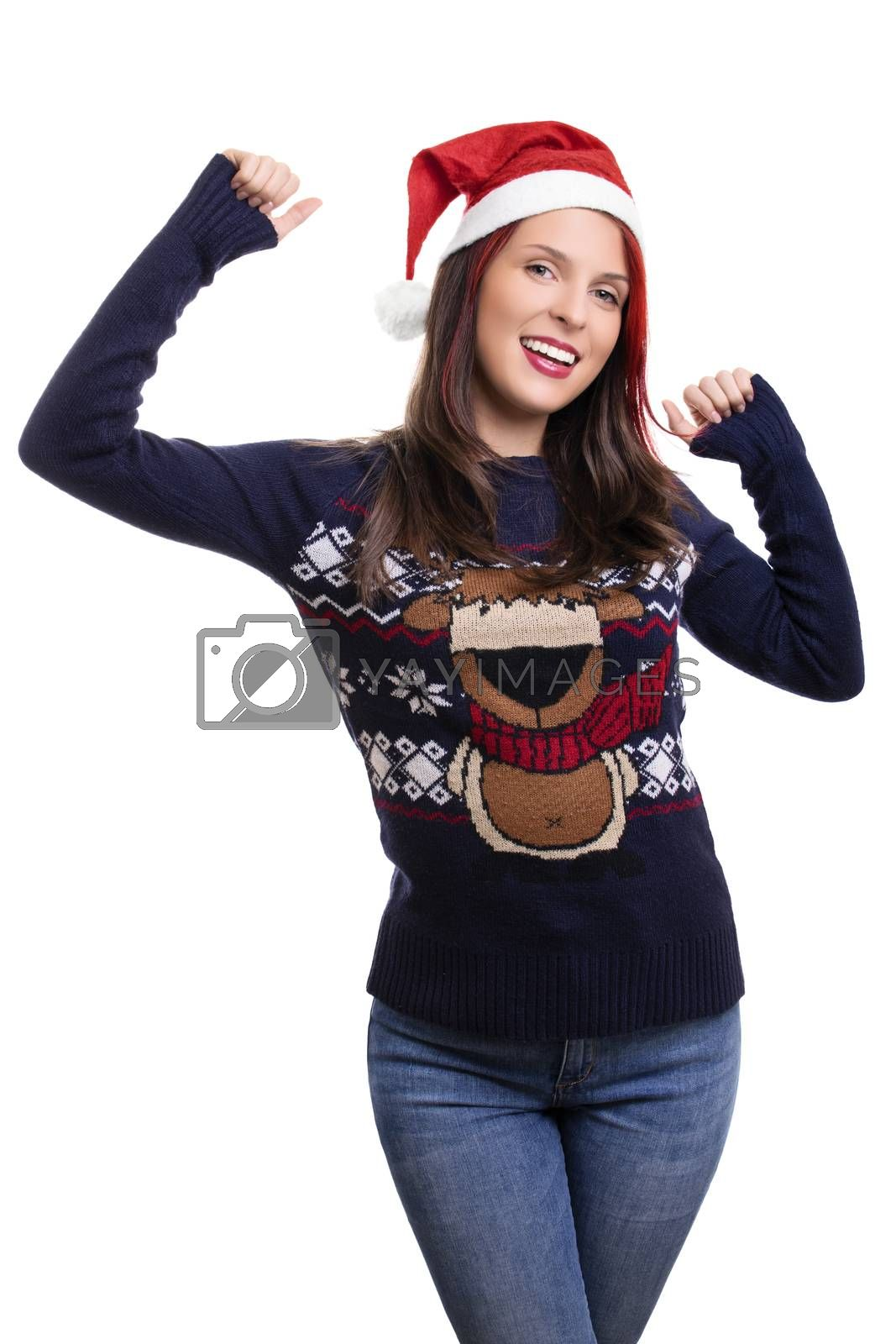 Beautiful young smiling girl wearing a Christmas hat and sweater, raising her hands in celebration, isolated on white background. Christmas and New Year concept.