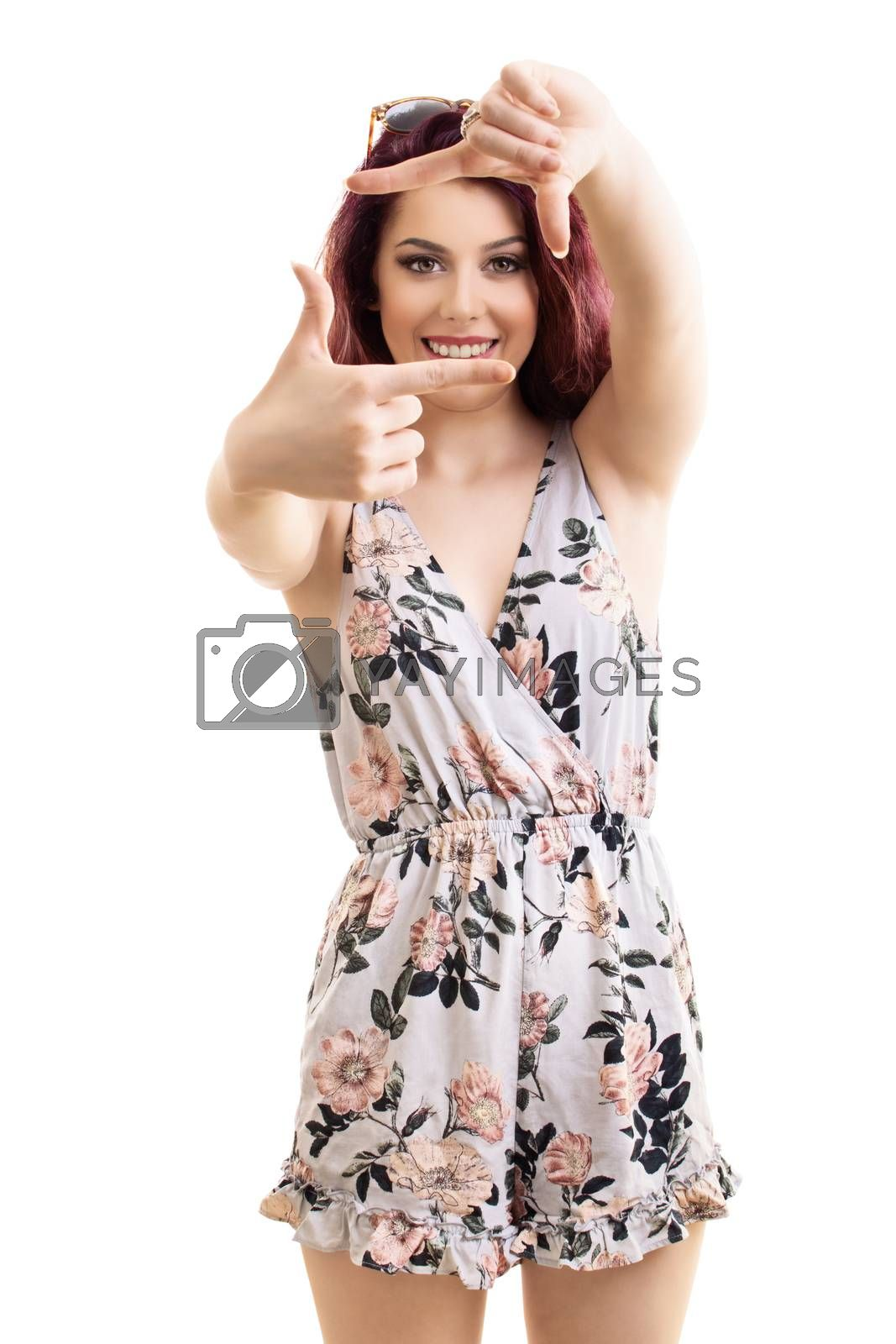 Portrait of a fashionable young smiling attractive woman making a camera frame with her hands and fingers, isolated on white background. Copy Space. Creativity and photography concept.