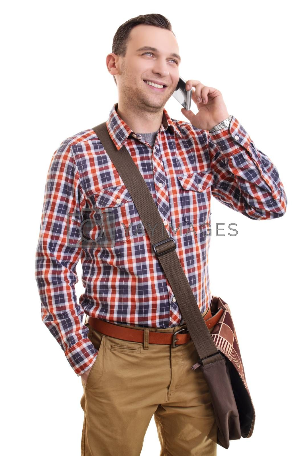 Communication concept. Portrait of a handsome smiling casual man in plaid shirt and a shoulder bag talking on mobile phone, isolated on a white background.