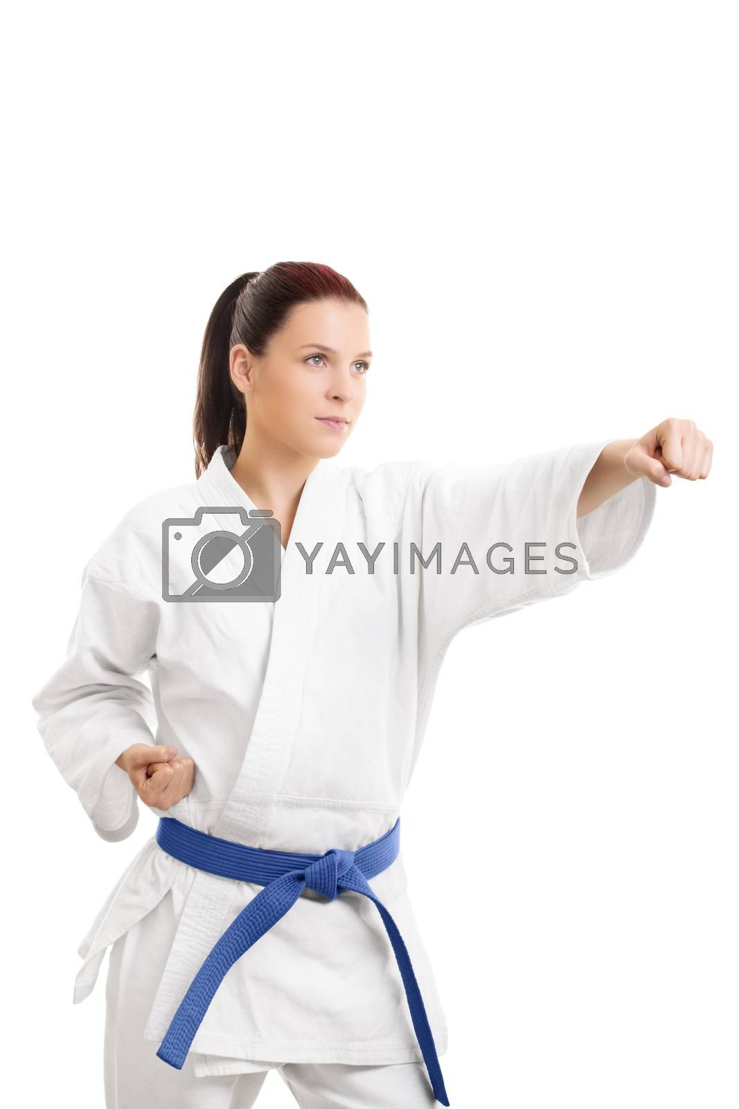 Martial arts concept. Portrait of a beautiful young girl in a kimono with blue belt punching, isolated on white background.