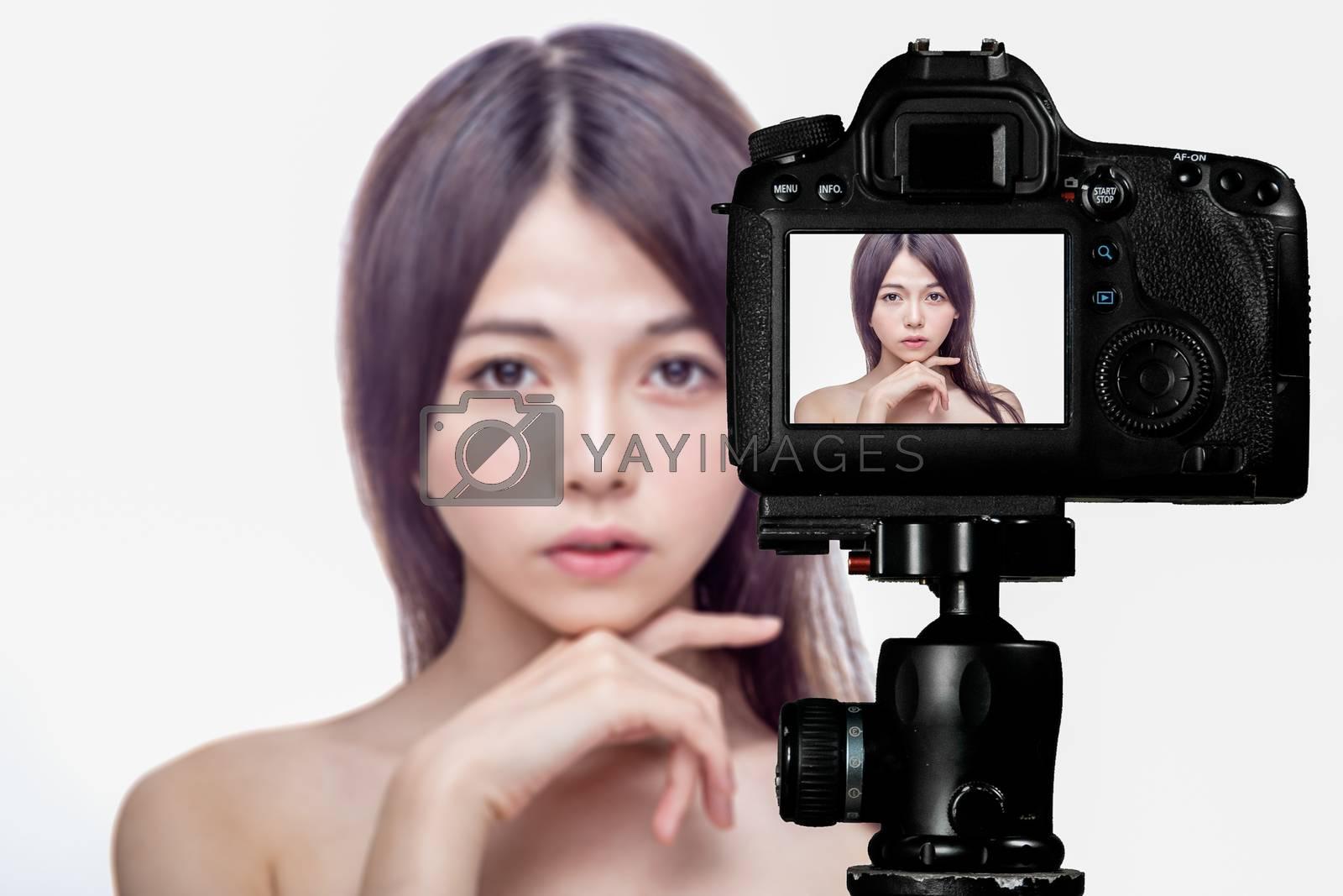 Asian American beauty vlogger creating content for social media vlog, behind camera shot