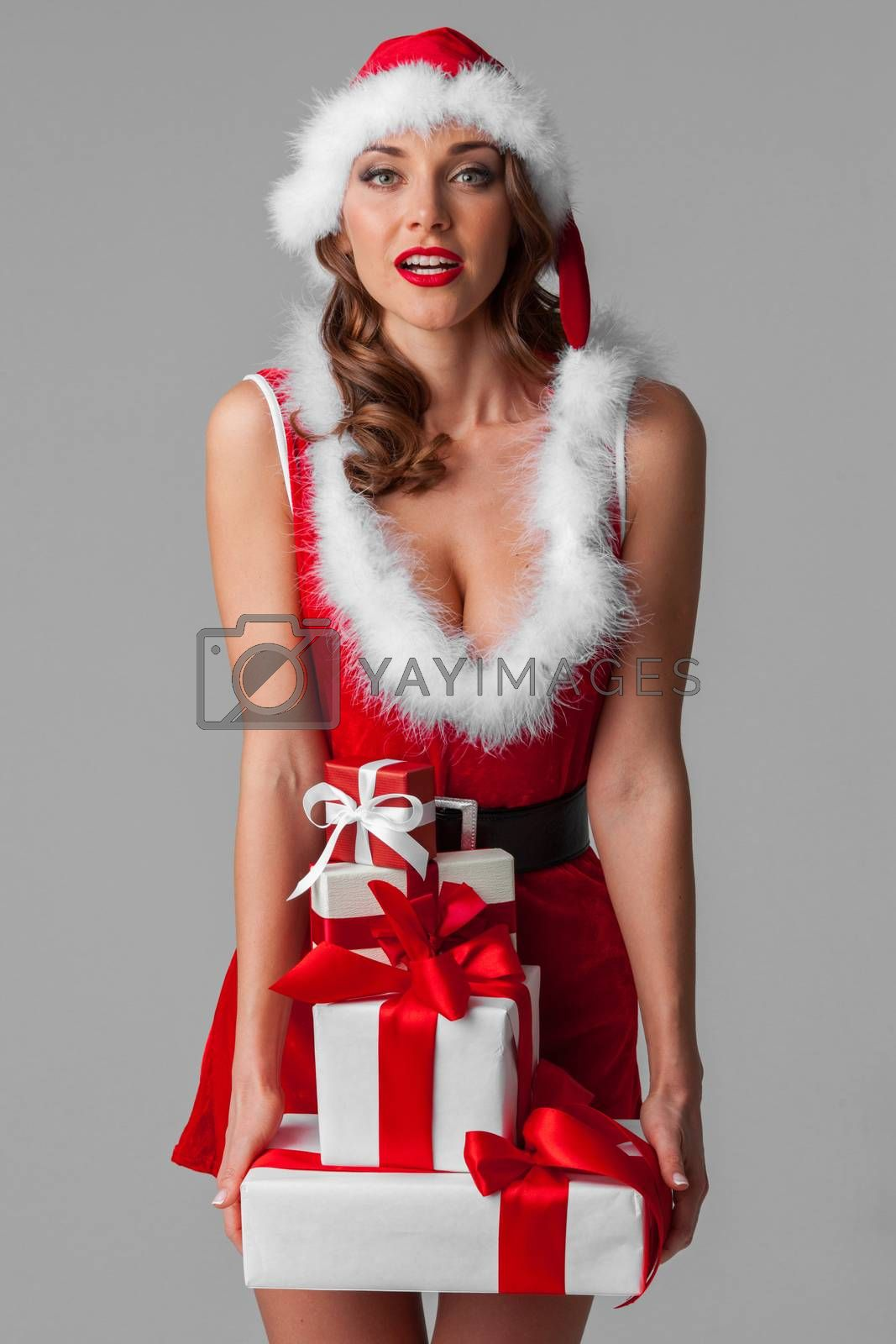 Sexy Mrs santa claus girl holding heavy stack of christmas gifts