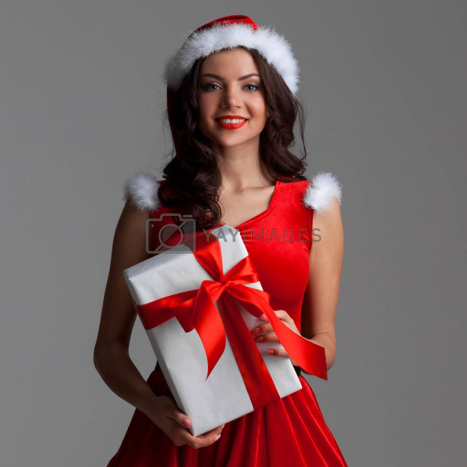 Smiling cute girl in red christmas outfit holding gift box on gray background
