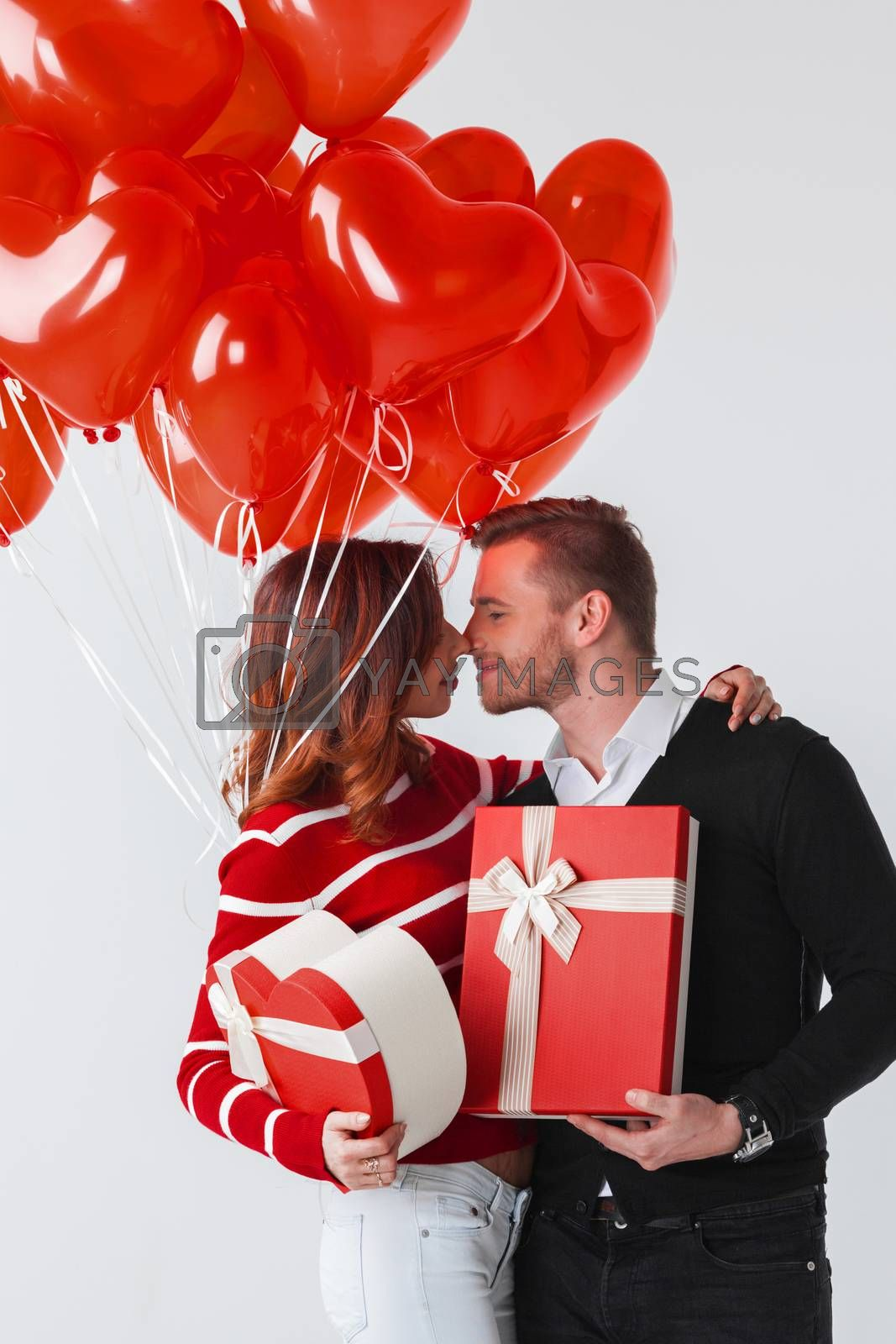 Happy smiling couple holding valentines day gifts and red balloons on white background