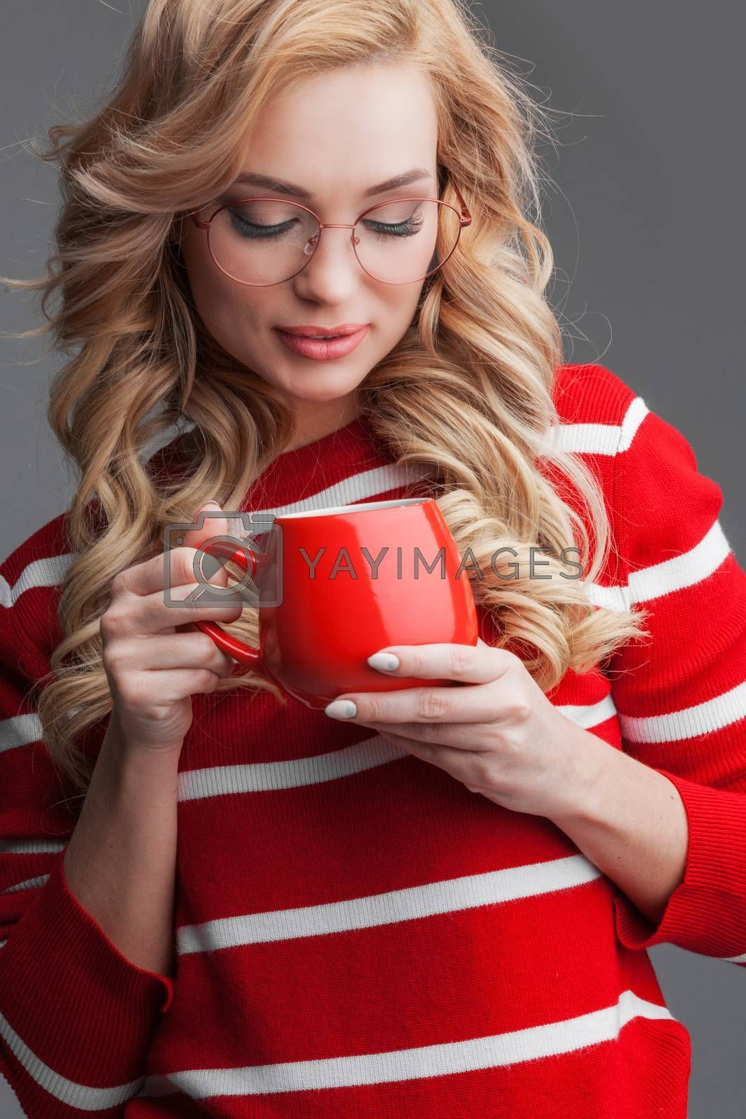 Beautiful blonde woman in glasses holding red cup of drink Christmas Valentines day concept