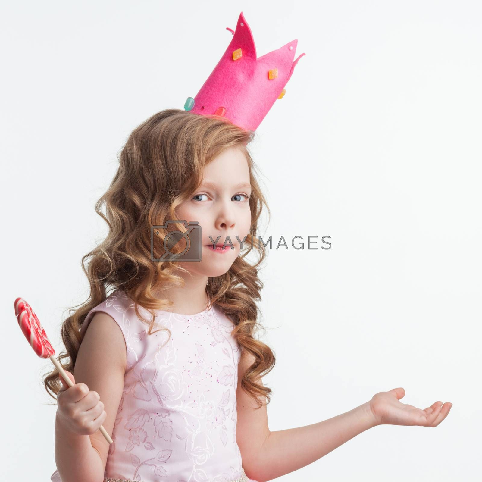 Beautiful little candy princess girl in crown holding big lollipop and posing with hands up in air saying, why, i dont know, so what isolated on white background
